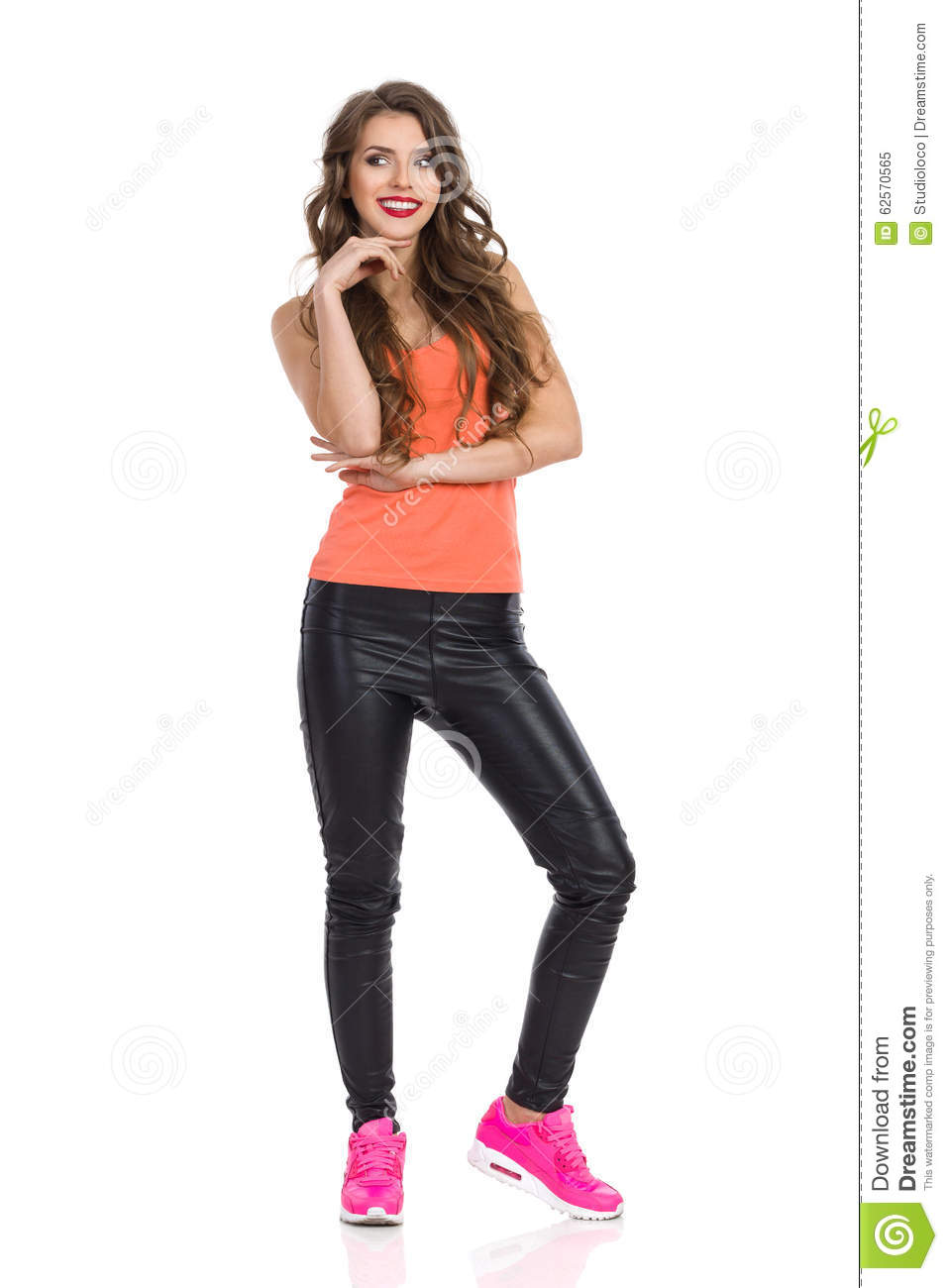 c8f68a300 Smiling young woman in orange shirt, black leather trousers and pink  sneakers standing, holding hand on chin and looking away.