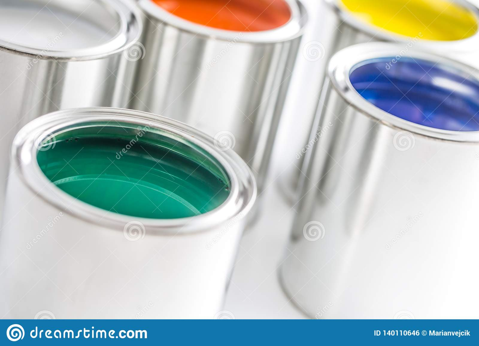 Full of multicolored paint cans on white table