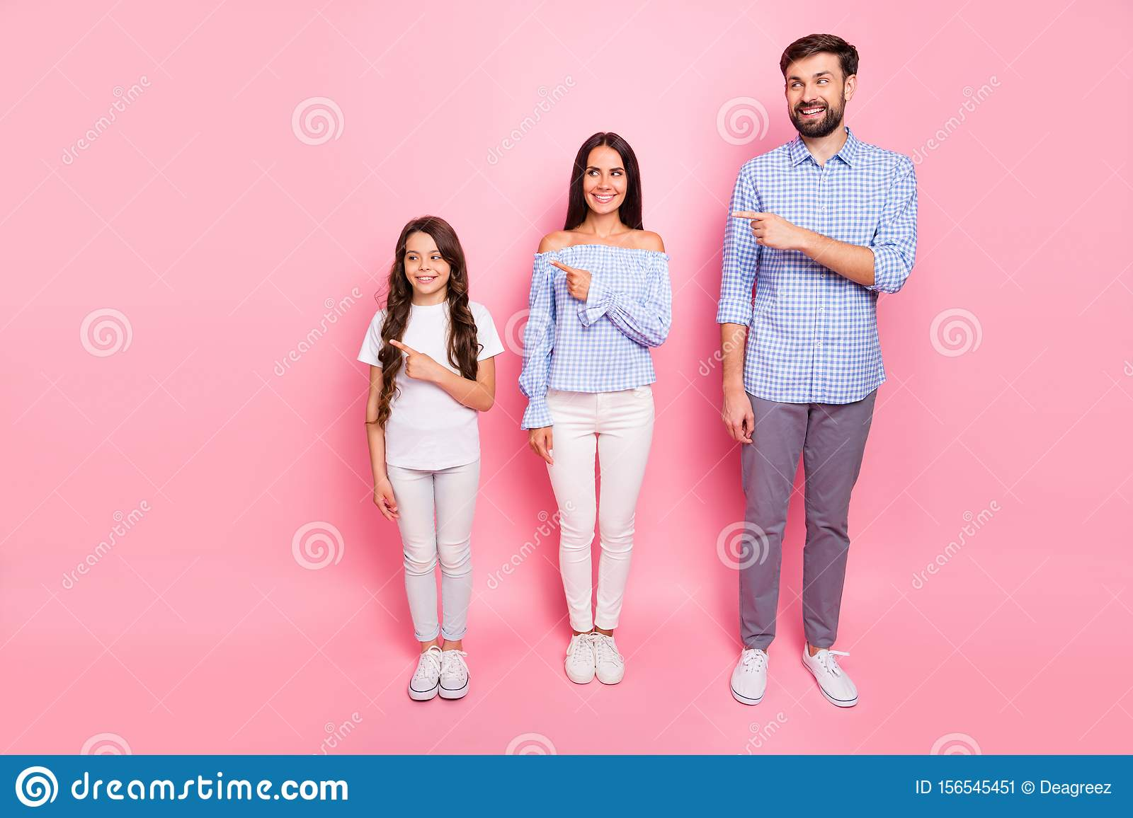 Full size photo of charming family with brunet hair pointing at copy space with beaming smile wearing plaid shirt