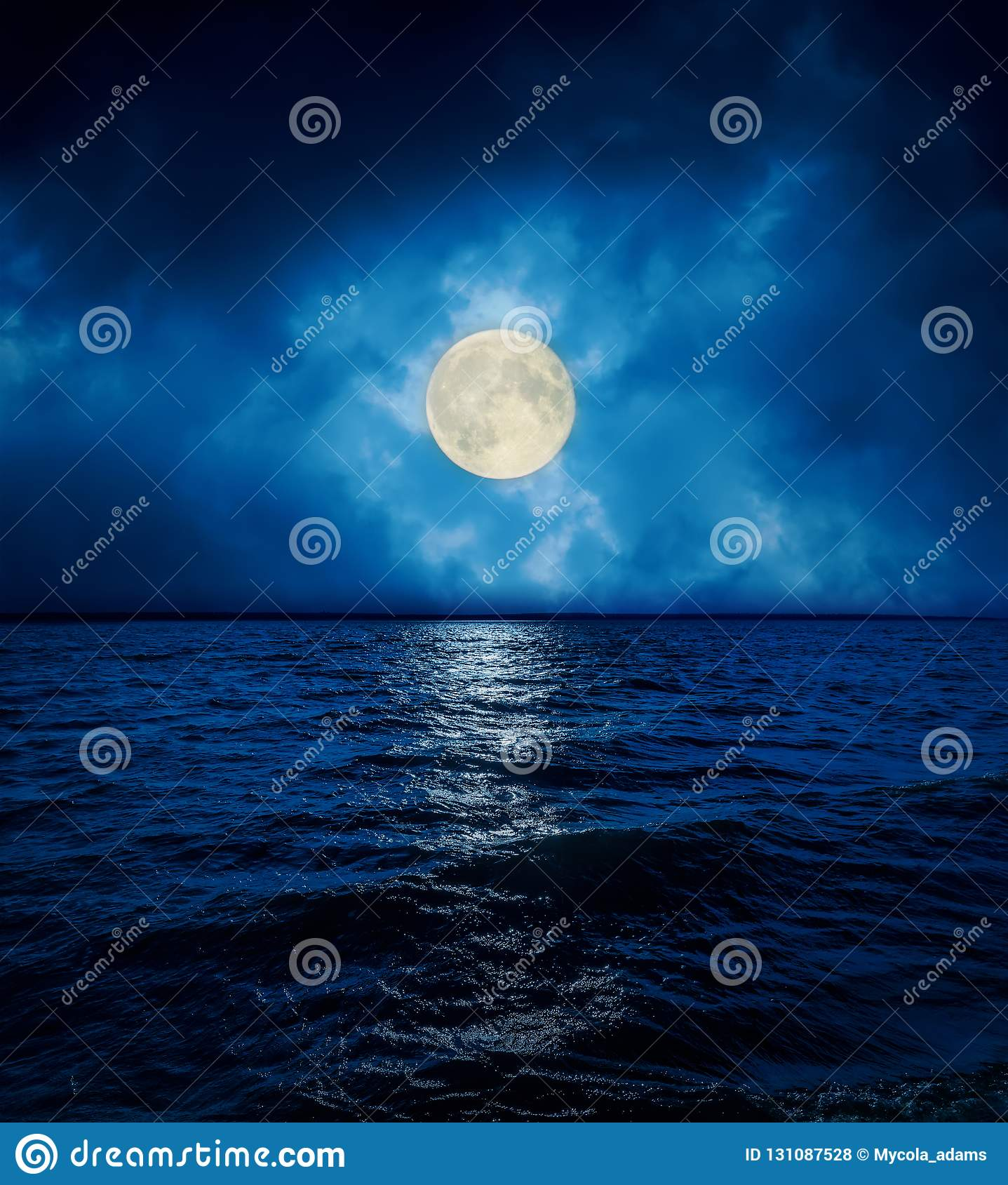 Full moon in dramatic clouds over dark water