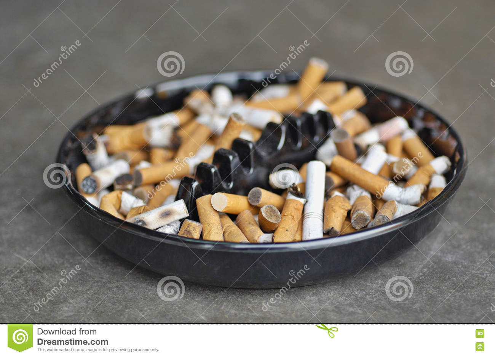 Fullt askfat av cigaretter på tabellen, närbild