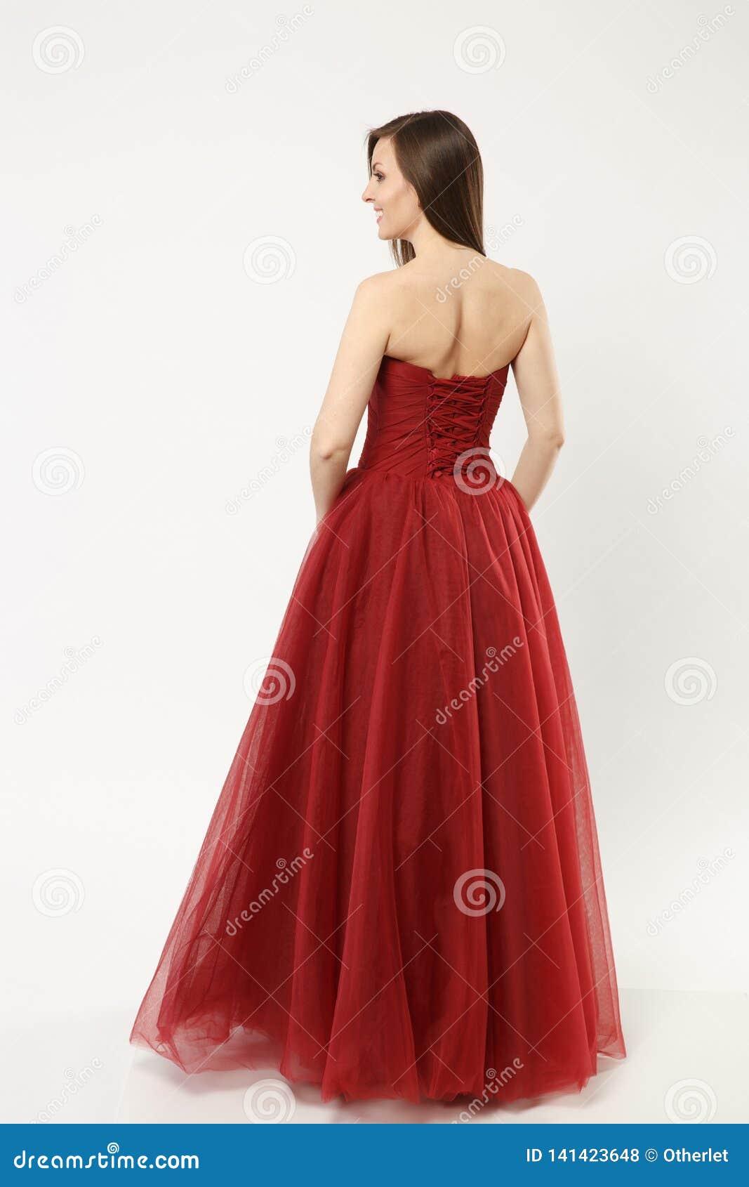 Fullt längdfoto av kvinnan för modemodell som bär elegant posera för kappa för aftonklänning som rött isoleras på vit väggbakgrun