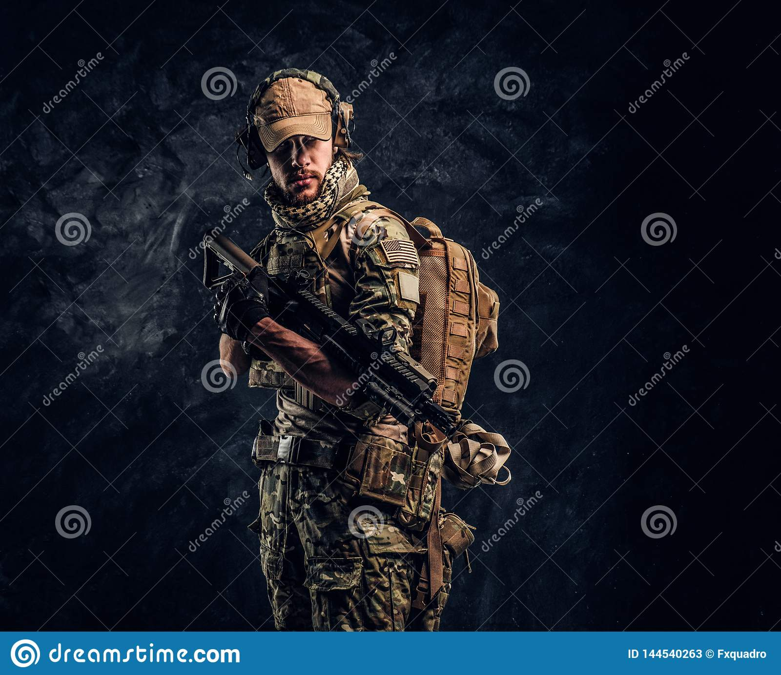 Fully equipped soldier in camouflage uniform holding an assault rifle. Studio photo against a dark wall