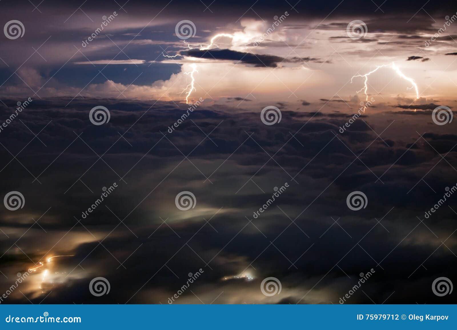 Fulmini multipli sopra la valle coperta di nuvole