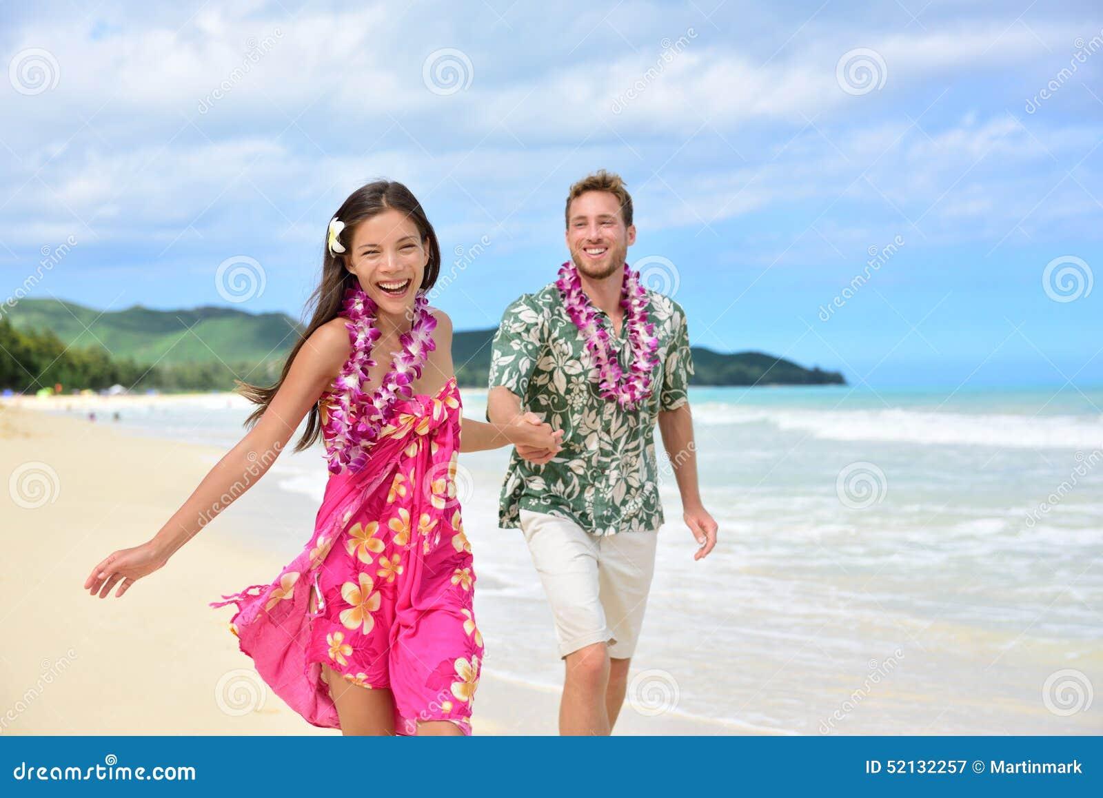 Fun Couple On Beach Vacations In Hawaiian Clothing Stock Photo