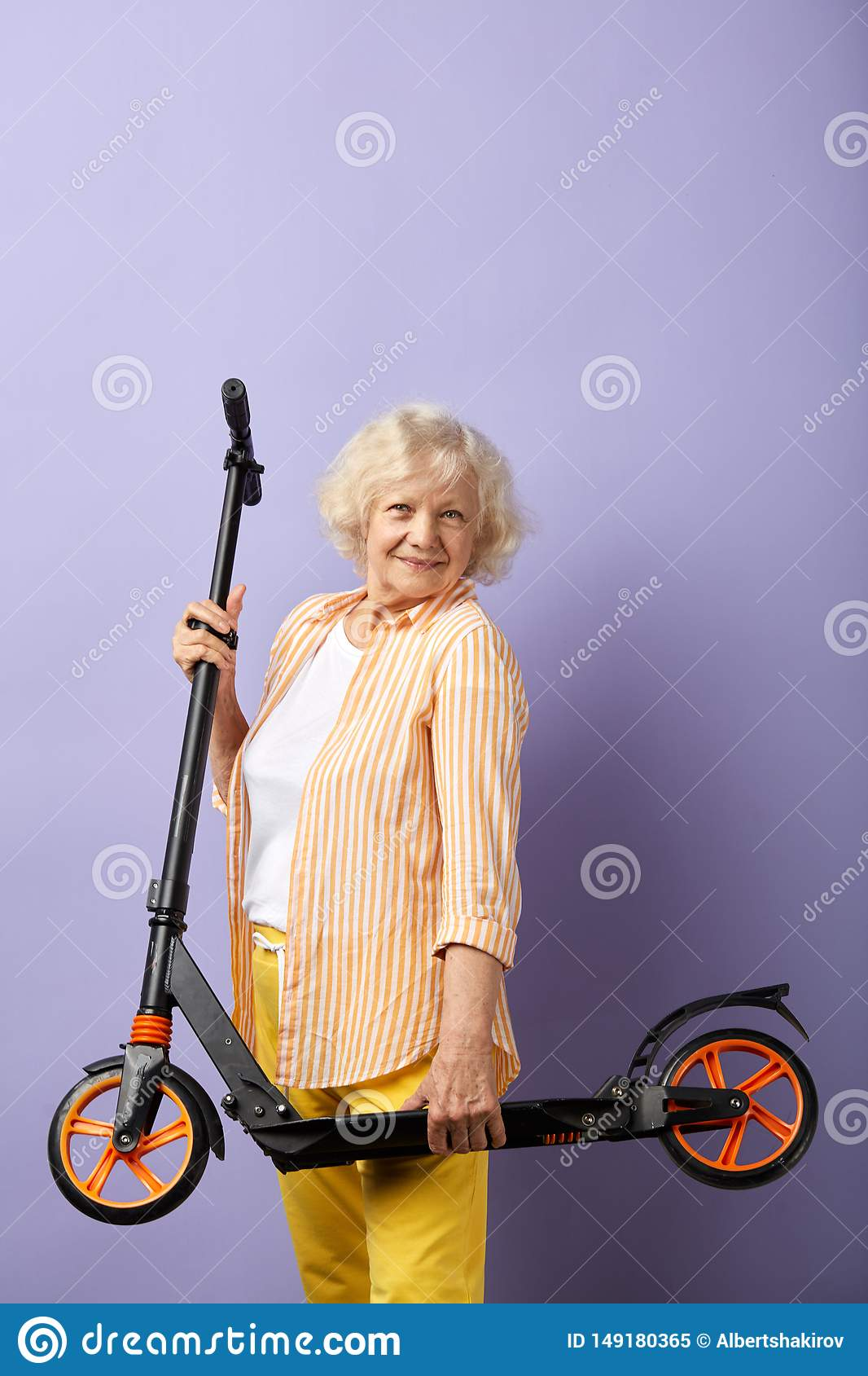 So fun. Happy elderly woman keeps in hands scooter ready for a ride.