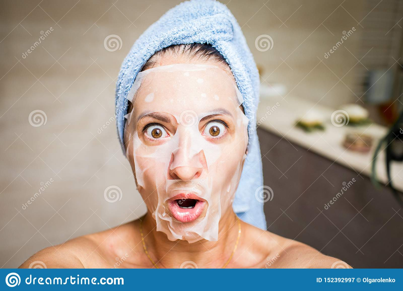 Fun selfie of a young woman with white mask on her face and light blue towel on her head