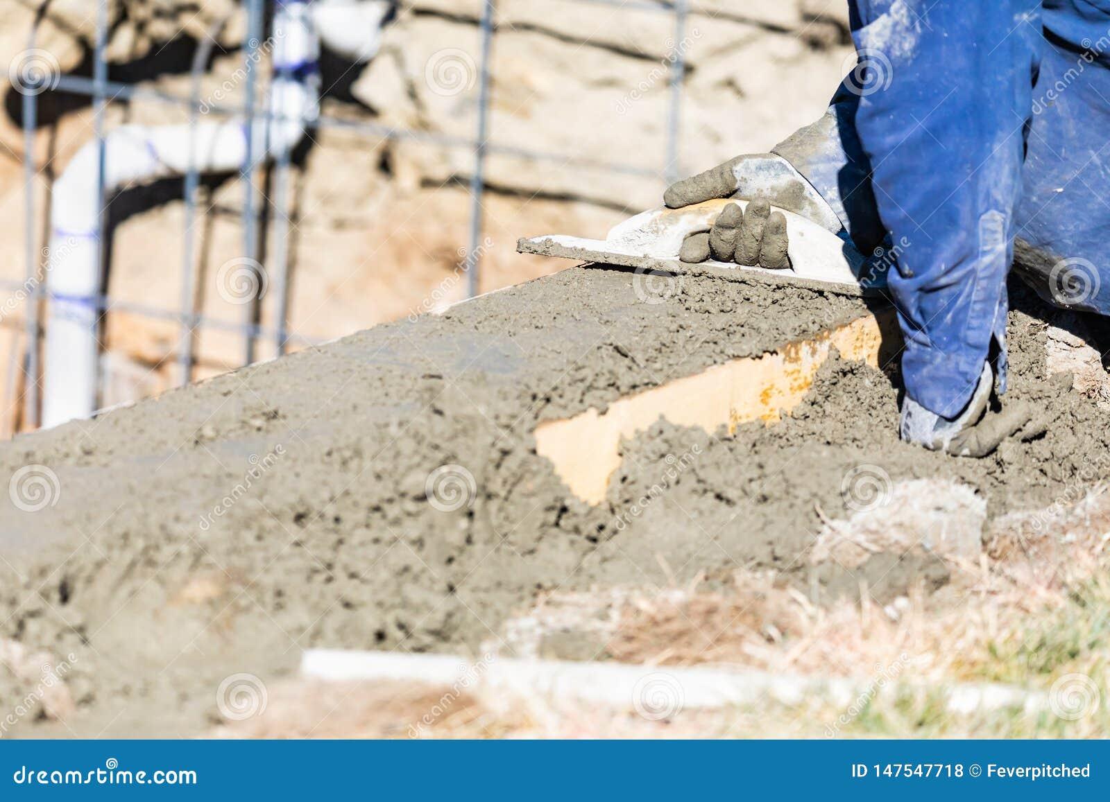 Funcionamento do trabalhador da constru??o da associa??o com o flutuador de madeira no concreto molhado