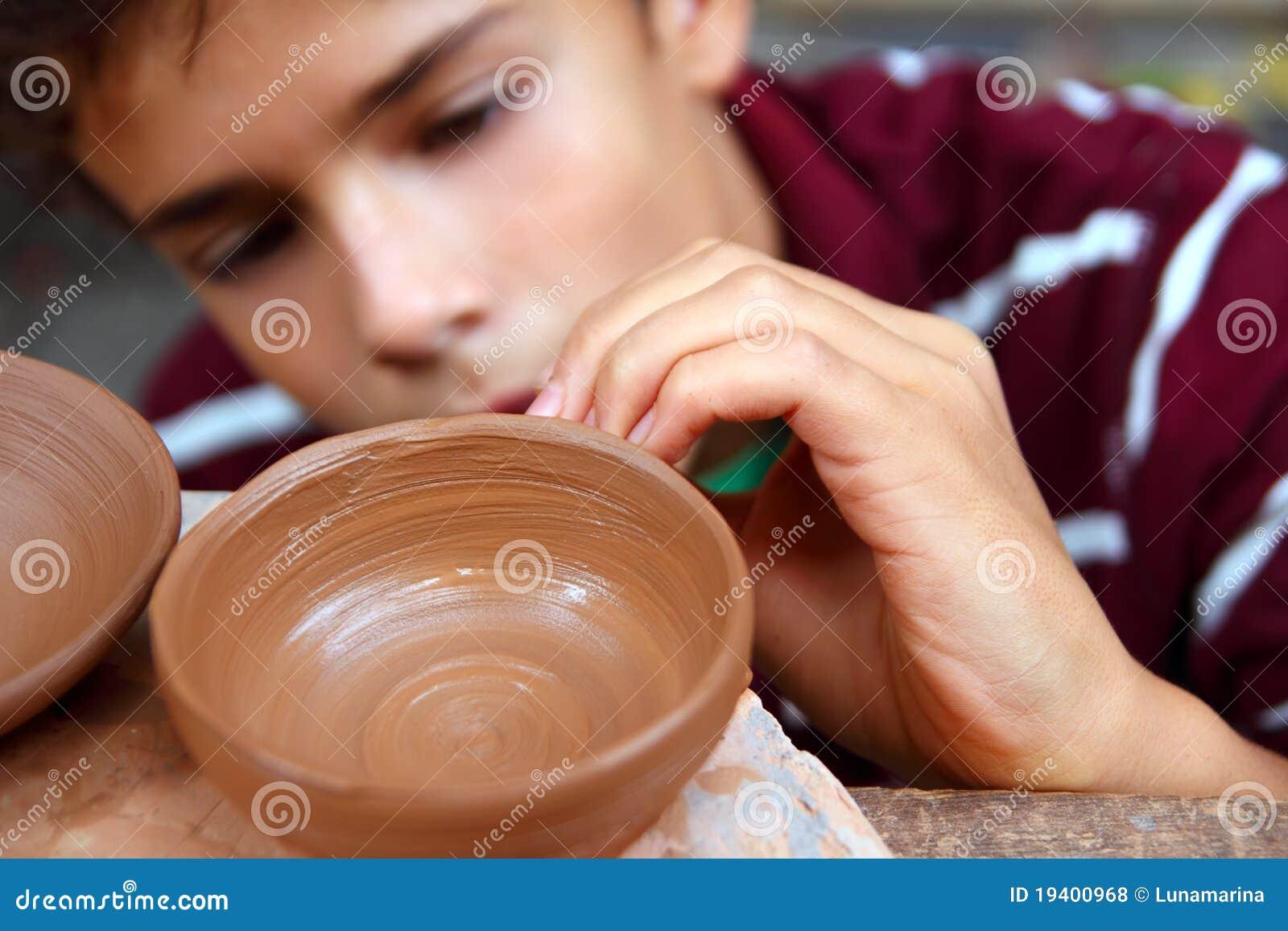 Funcionamiento adolescente del tazón de fuente de la arcilla del alfarero del muchacho