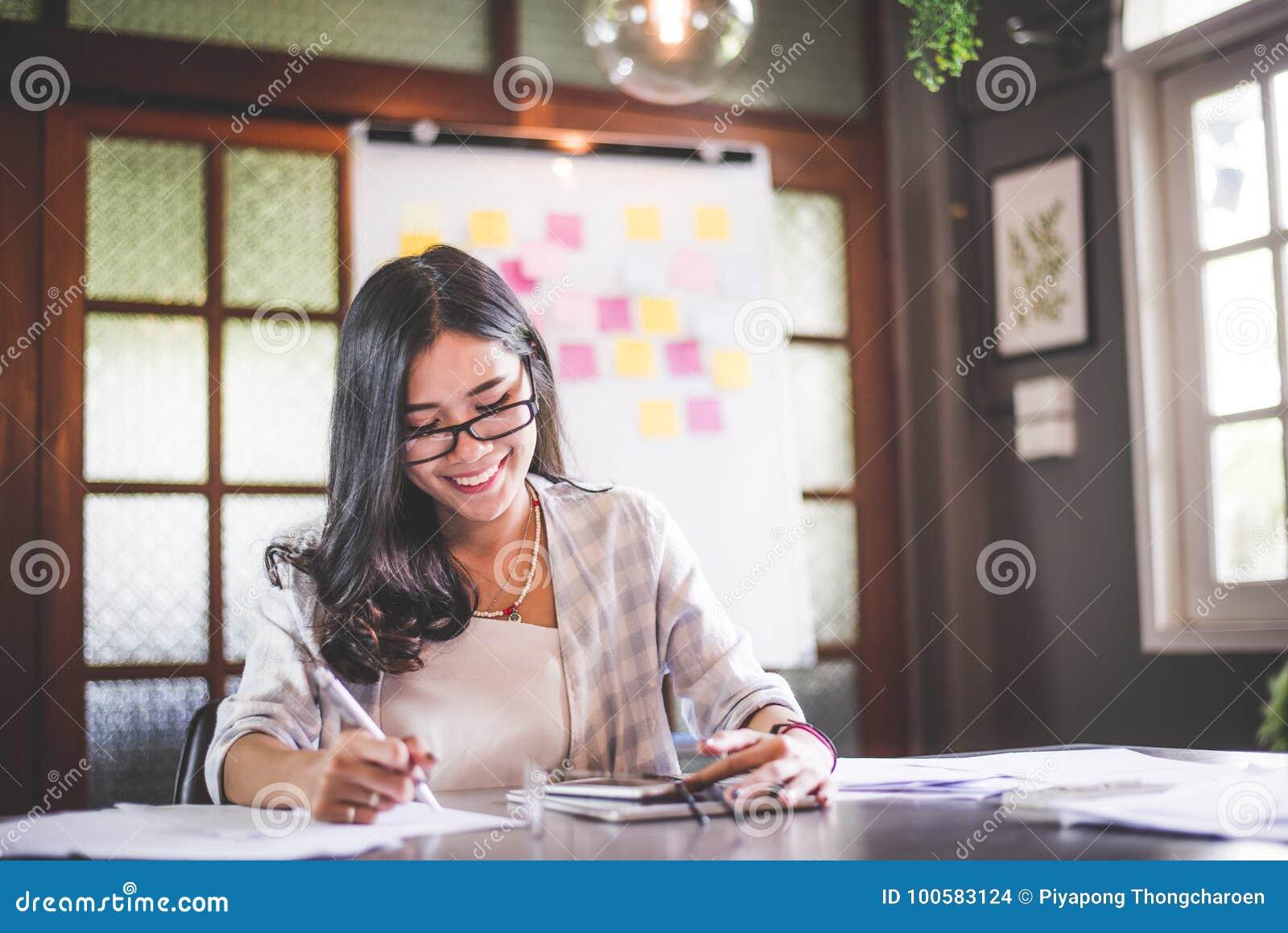 Funcionamiento de la mujer del negocio y nota asiáticos hermosos de la escritura