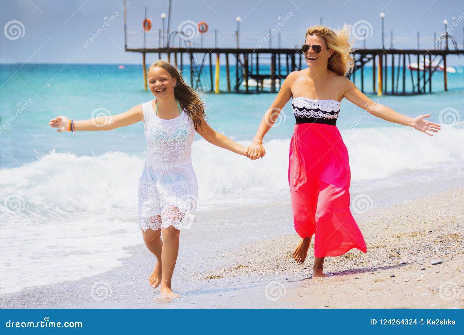 Funcionamiento feliz de la hija de la madre y del adolescente de la familia, risa y juego en la playa