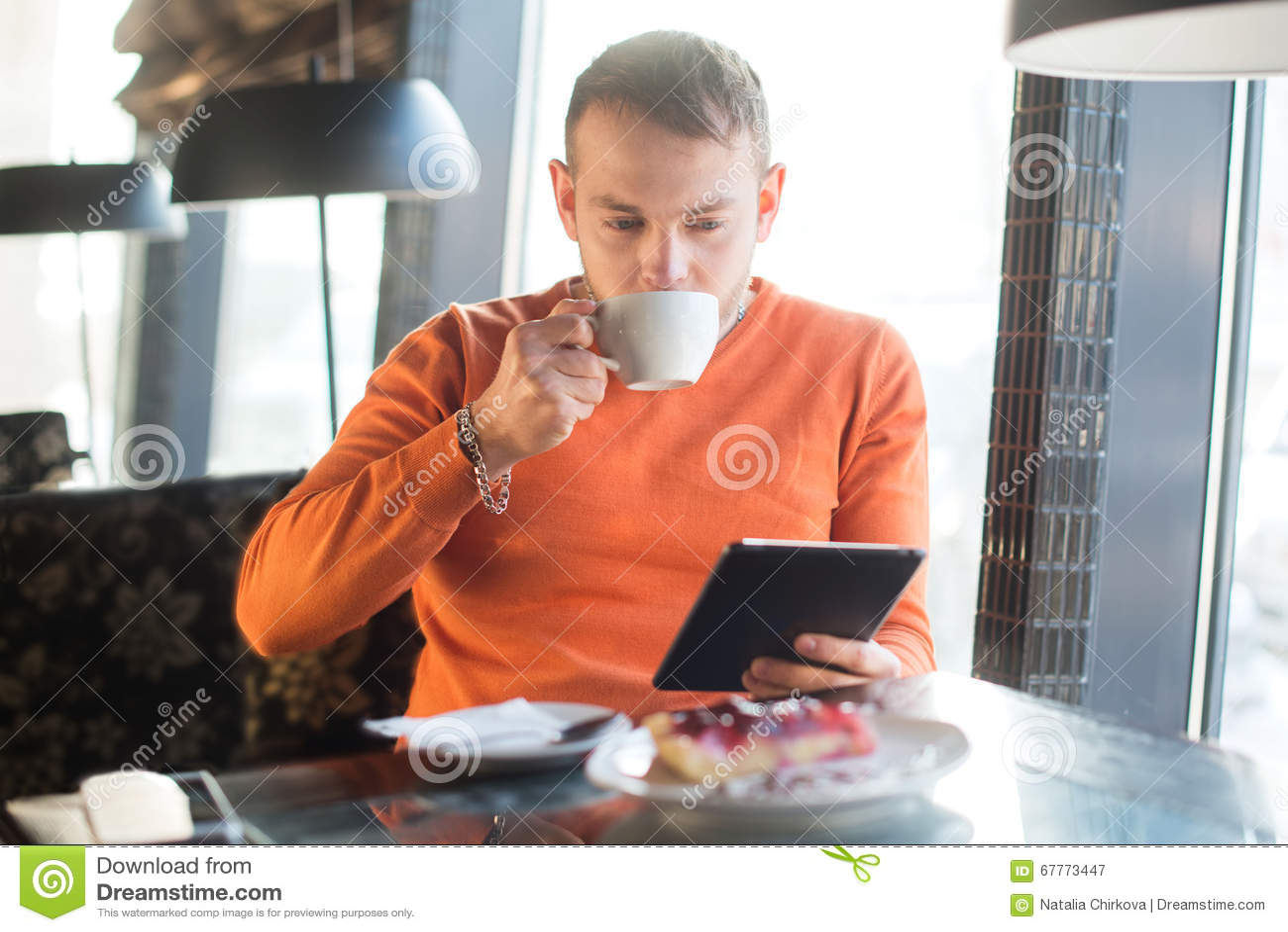 Funcionamiento hermoso del hombre joven, mirando en la tableta mientras que goza del café en café
