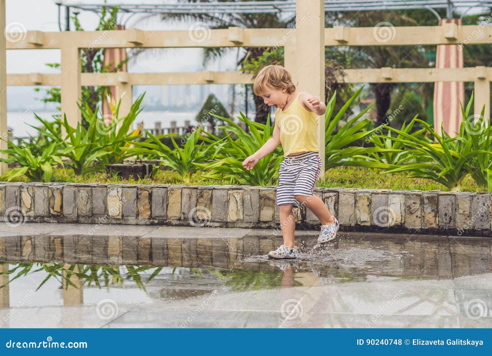 Funcionamientos del niño pequeño a través de un charco Verano al aire libre