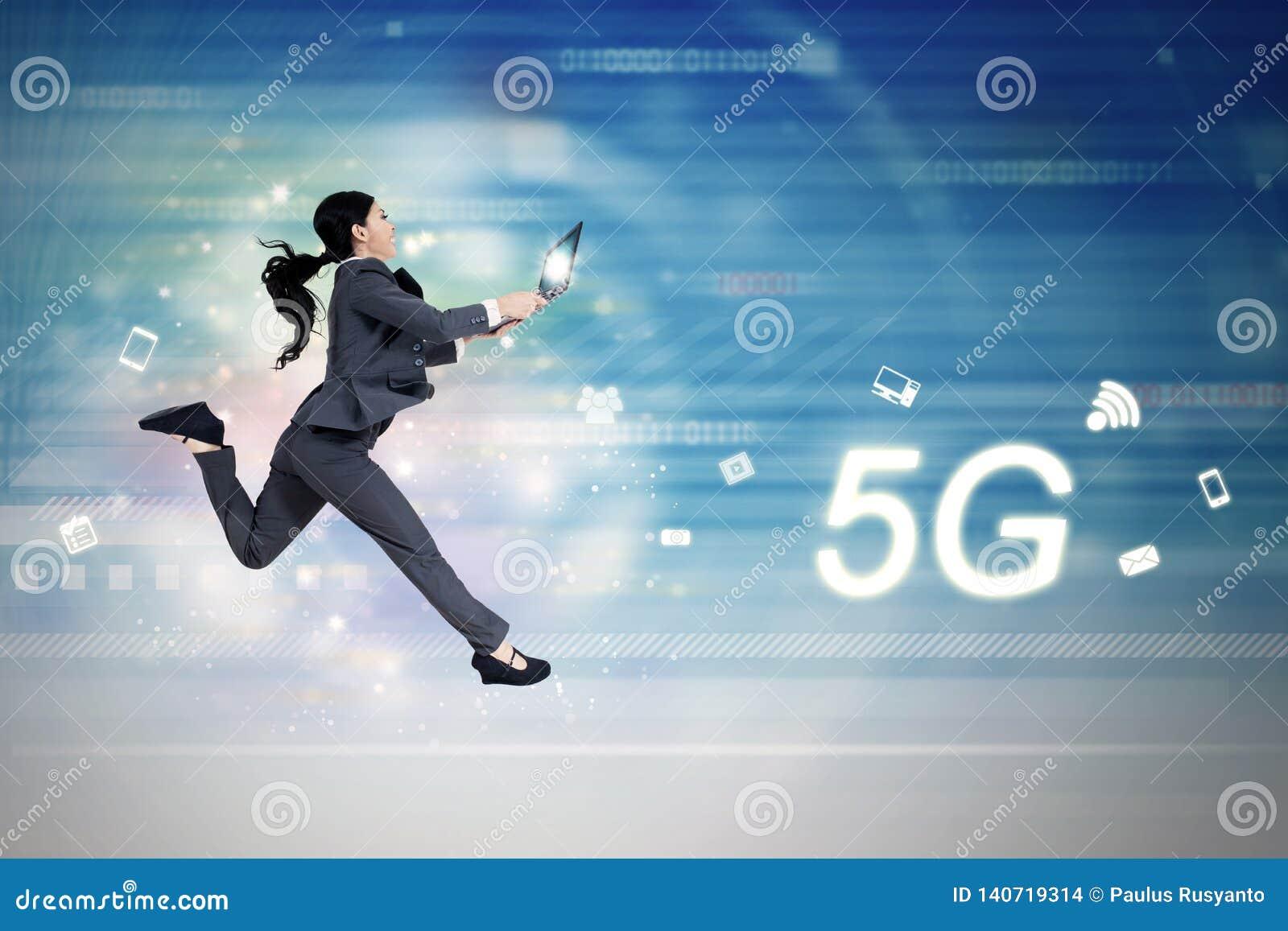 Funcionamientos del símbolo y de la mujer de la red 5G con el ordenador portátil