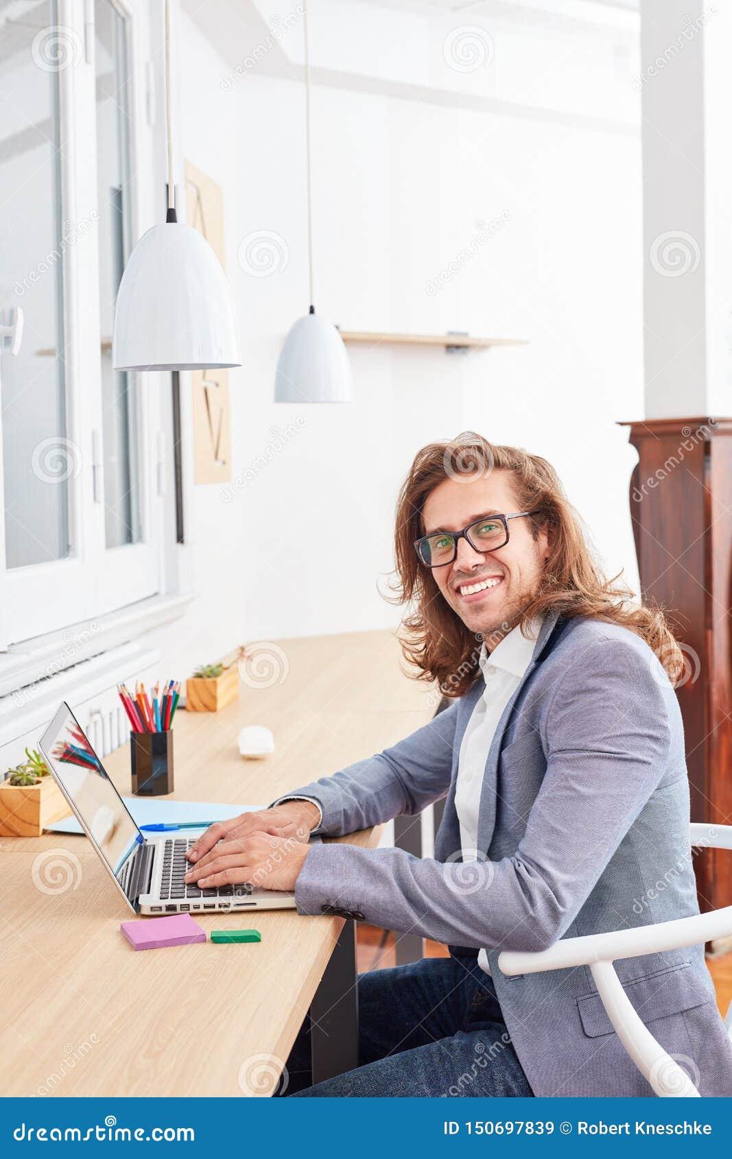 Fundador de lanzamiento joven creativo en el ordenador portátil