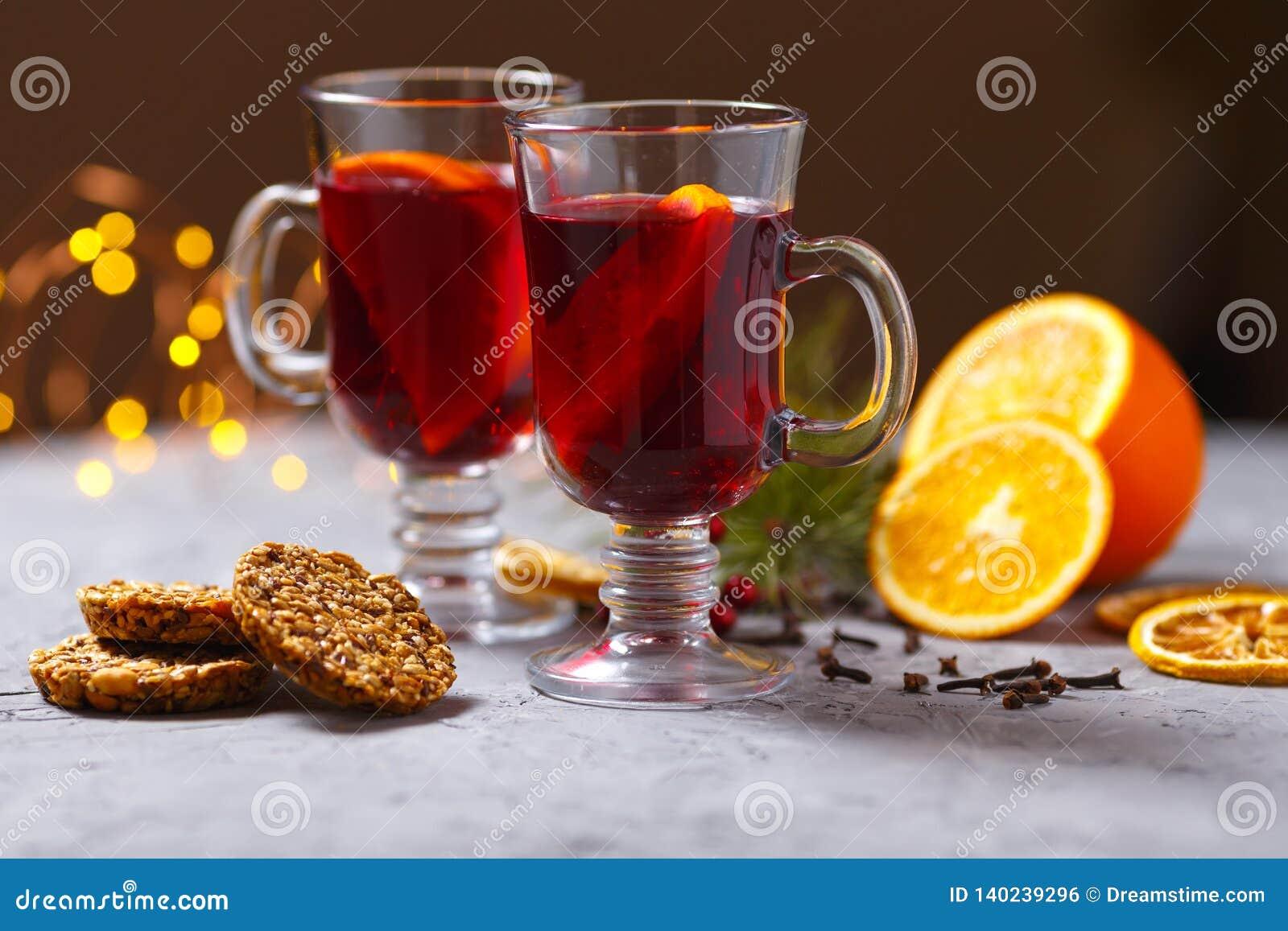 Funderat rött vin med kryddor och apelsinen på mörk bakgrund Värmedrink