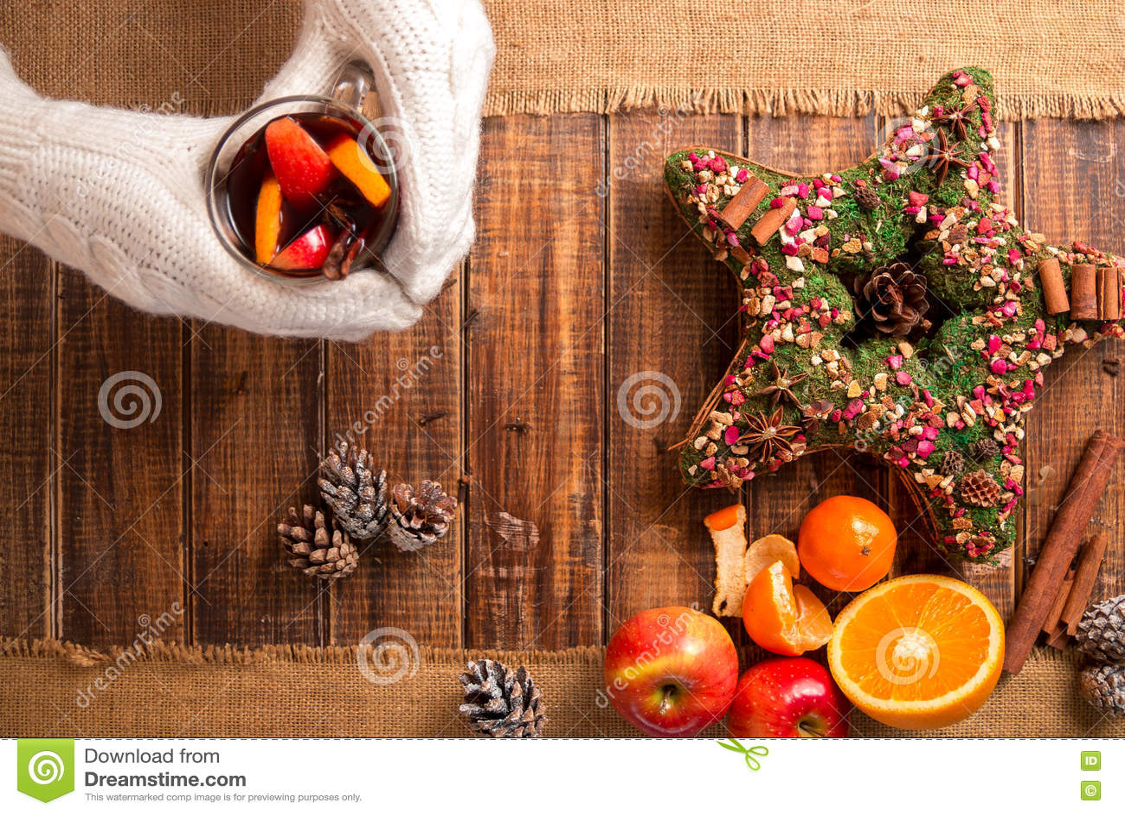 Funderat vin i kvinnahänder i vit stack handskar nära kryddar och fruktingredienser på trätabellen Vintervärmedrink christ