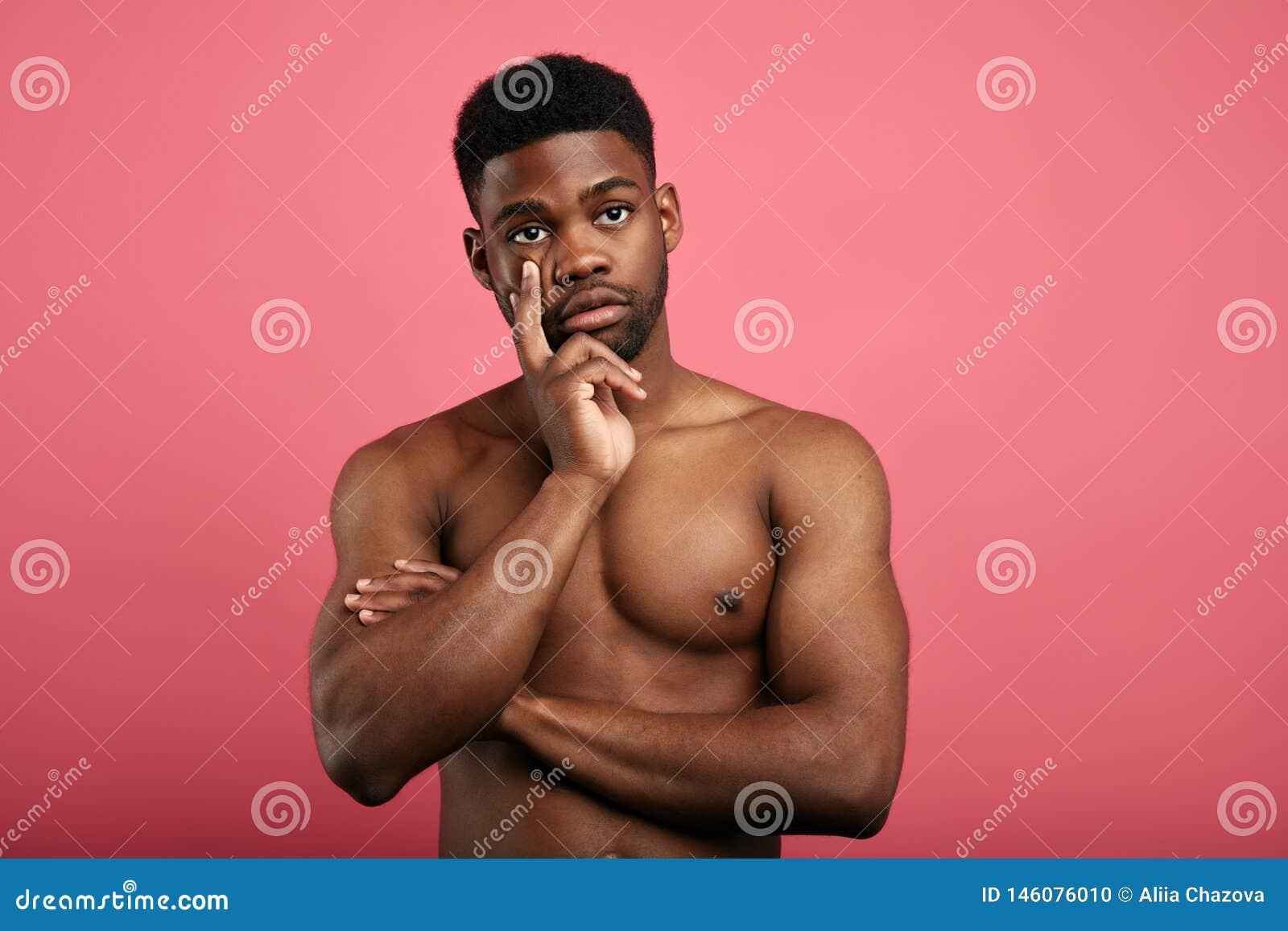 Fundersam grabb som trycker på hakan med fingret, tänker eller betraktar och att göra beslutet som föreställer