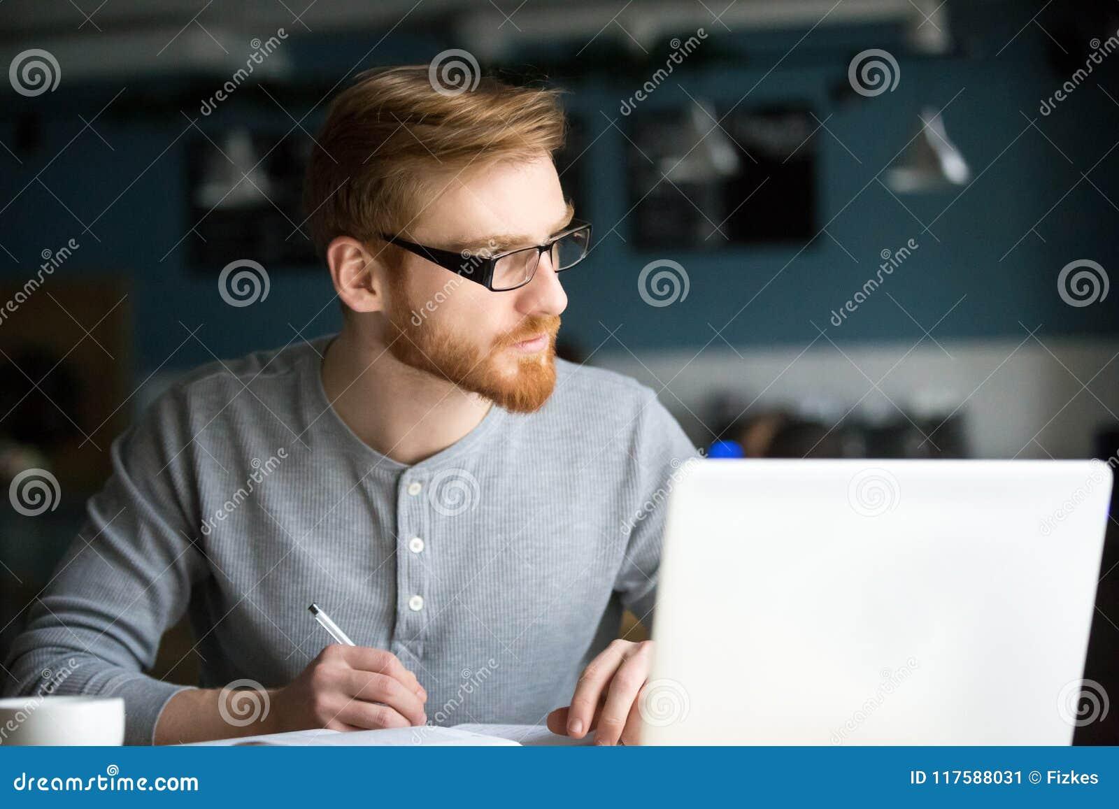 Fundersam man som tänker av ny idé som skriver anmärkningar i kafé