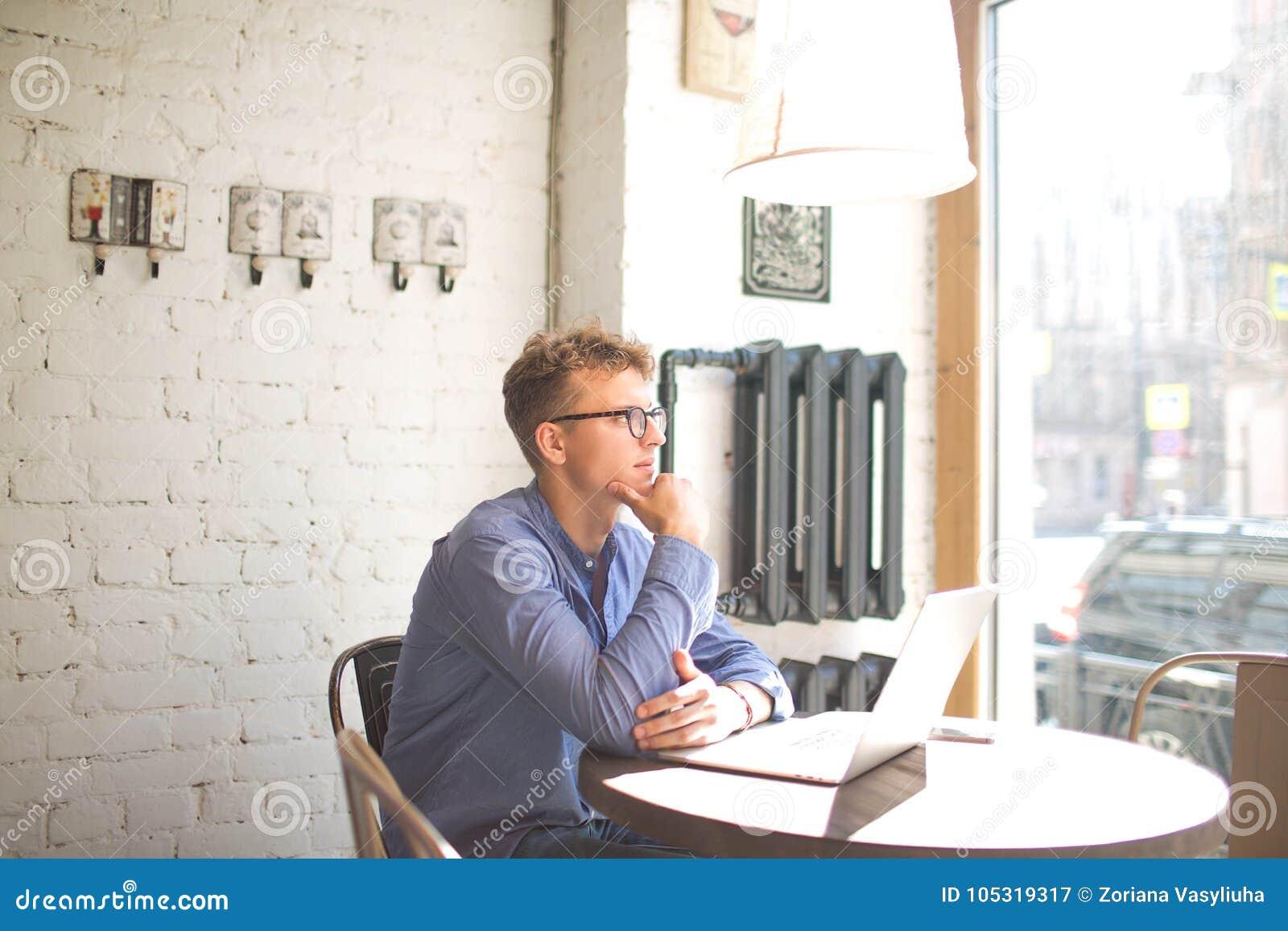 Fundersam manlig marknadsföringskoordinator som håller ögonen på i kaféfönster under arbete på netto-boken