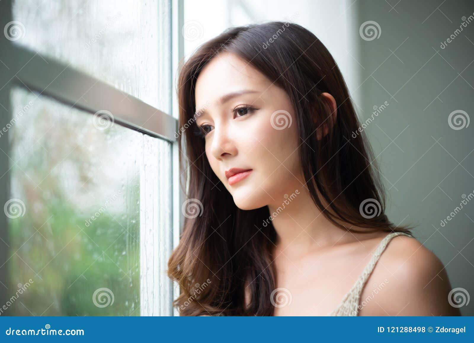 Fundersam ung asiatisk kvinna för Closeup som ser till och med exponeringsglasfönster med regndroppar på hennes hem Melankoliskt