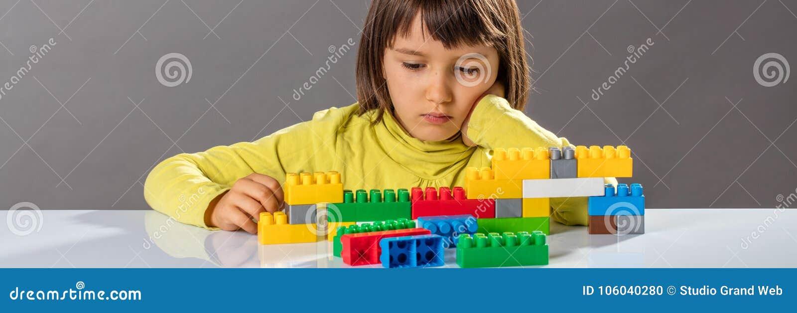 Fundersamt litet barn som ser hennes byggnadstegelstenar med fantasi