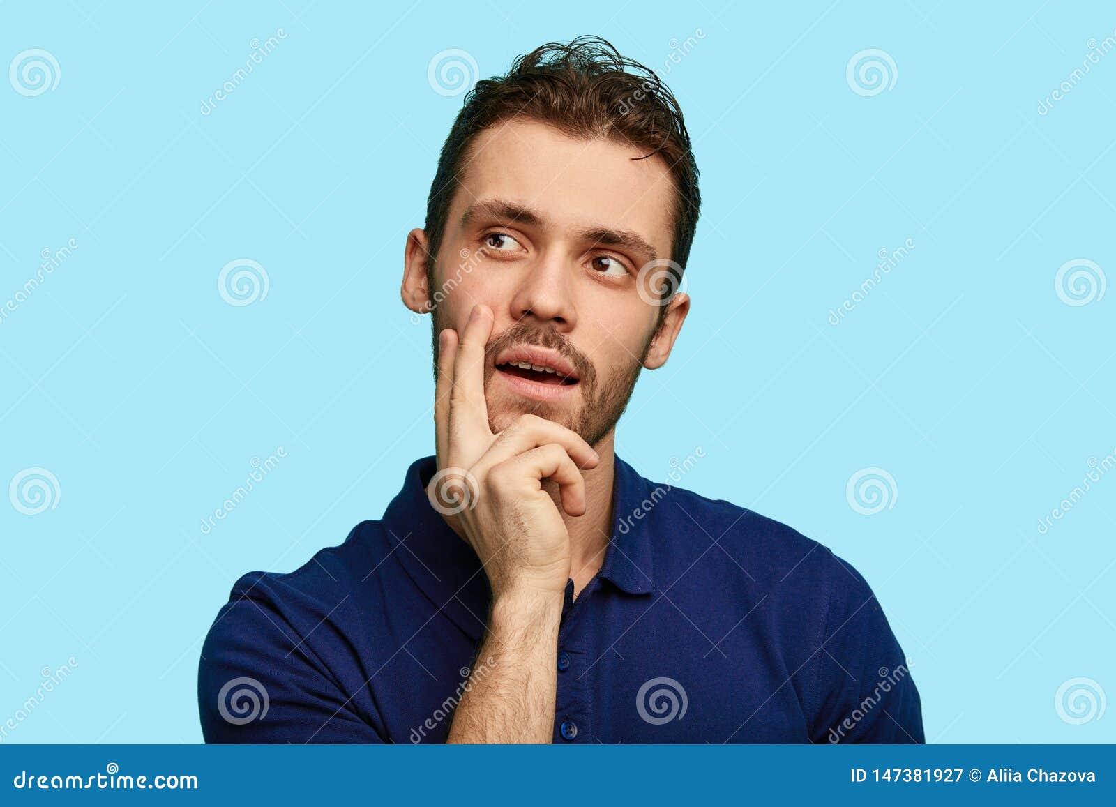 Fundersamt mananseende med handen på hakan och att se bort som isoleras över blå bakgrund