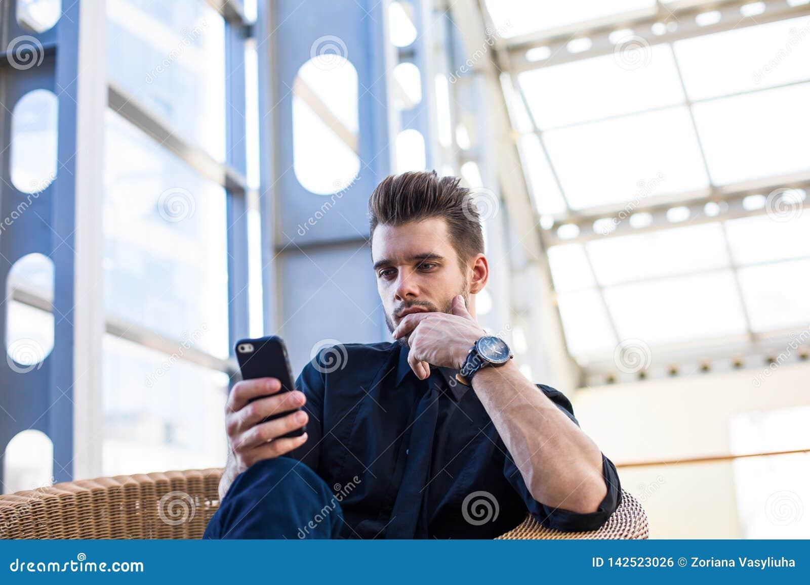 Fundersamt manledarskap som installerar apps på mobiltelefonen som sitter i företag under arbetsdag