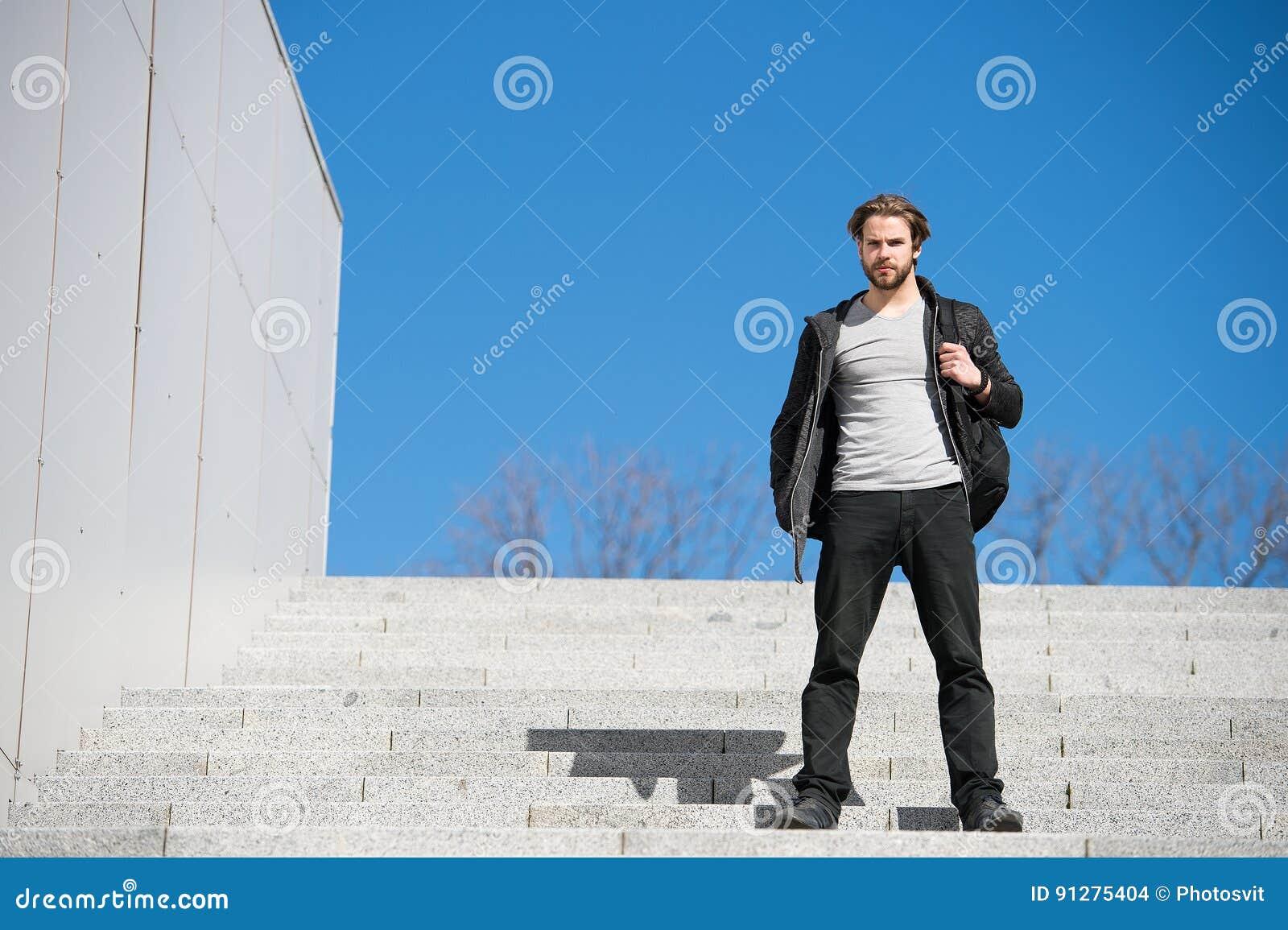 Fundersamt sammanträde för ung man på moment mot bakgrund för blå himmel
