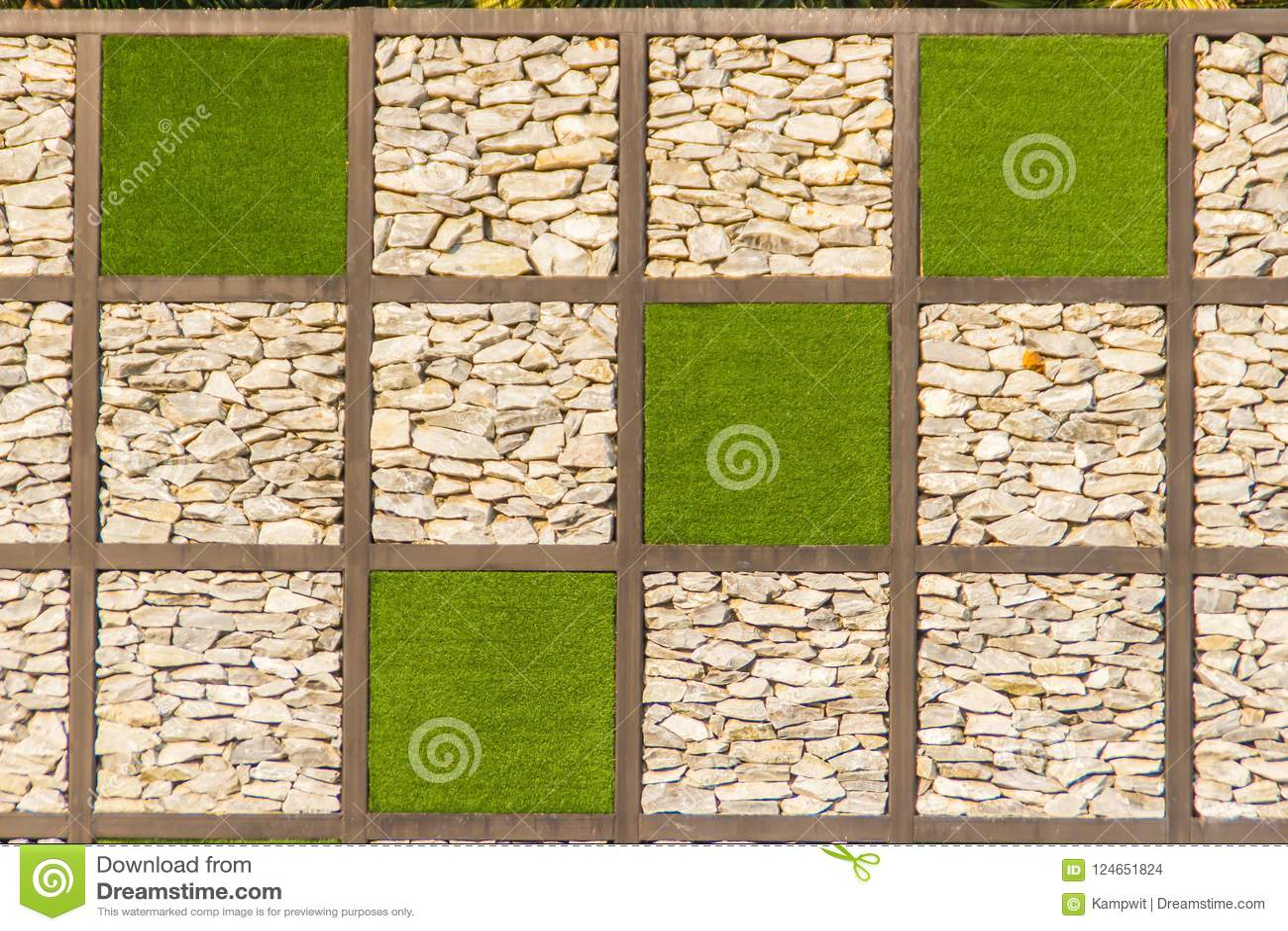 Fundo abstrato da parede de pedra do seixo do rio com quadro da grama verde Cobrir a forma do fundo da parede e do quadrado da gr