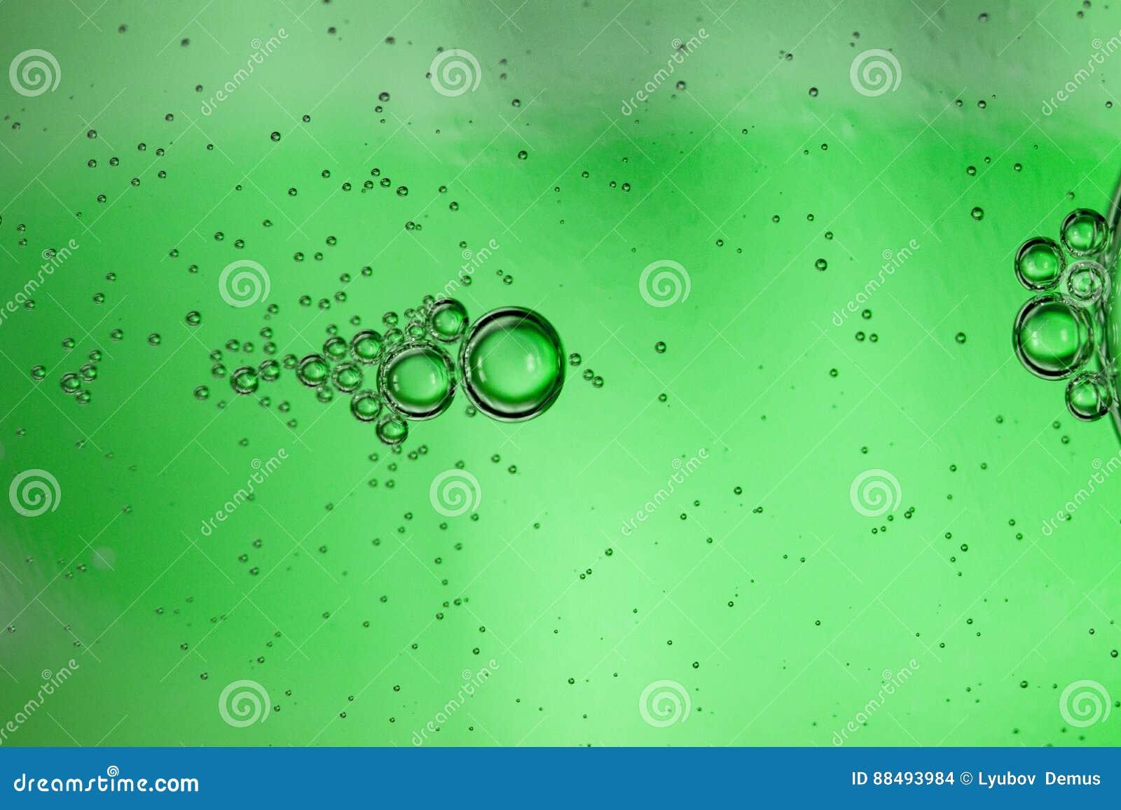 Fundo abstrato das bolhas da água carbonatada através de uma garrafa de vidro verde