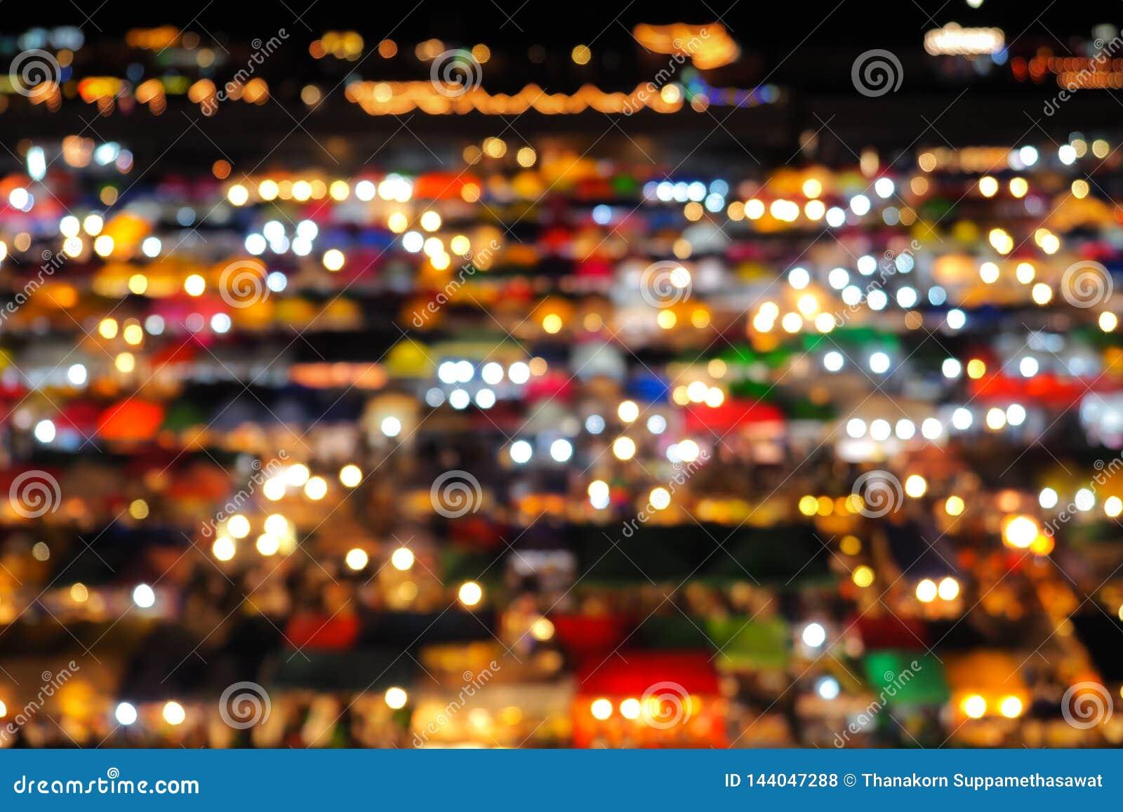 Fundo abstrato do bokeh do borrão da opinião alta do mercado da noite de construir a loja varejo e a iluminação da barraca colori