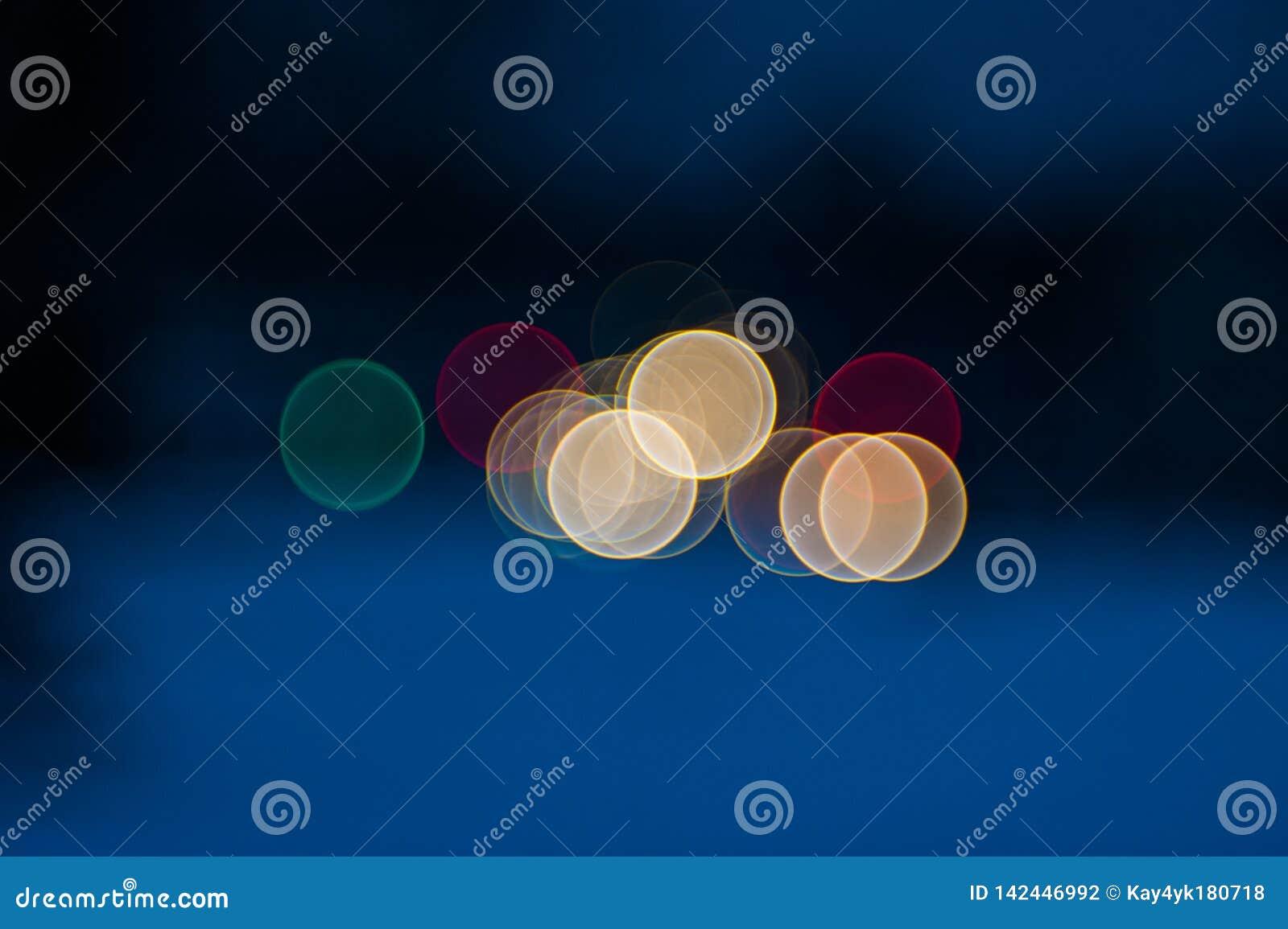 Fundo borrado bonito colorido do bokeh com espa?o da c?pia Textura festiva Pontos claros coloridos brilhantes em um escuro - azul