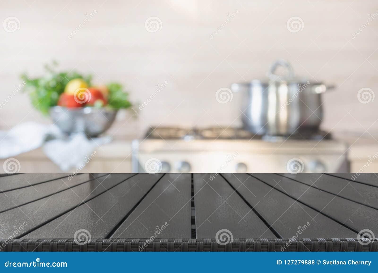 Fundo borrado Cozinha moderna com o tabletop de madeira vazio e espaço para você