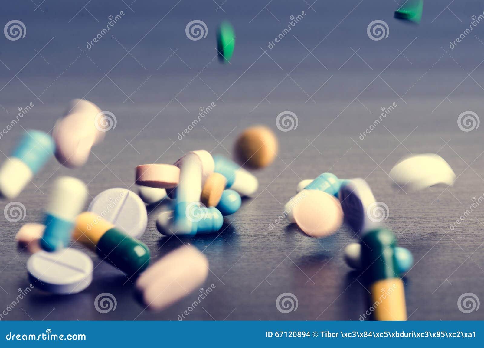 Fundo da farmácia em uma tabela escura Comprimidos da levitação Tabuletas em um fundo escuro que que cai para baixo Comprimidos M