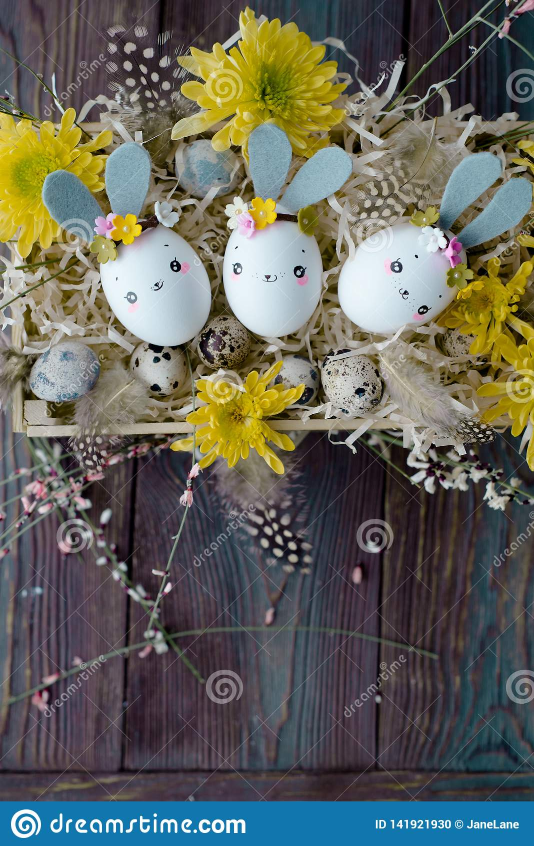 Fundo da Páscoa, coelhos caseiros da casca de ovo e crisântemo amarelo na caixa de madeira