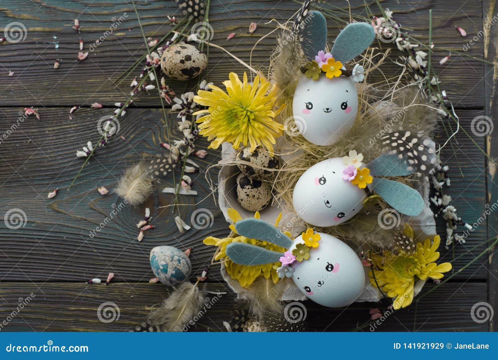 Fundo da Páscoa, coelhos caseiros das cascas de ovo e crisântemo amarelo em umas caixas de cartão