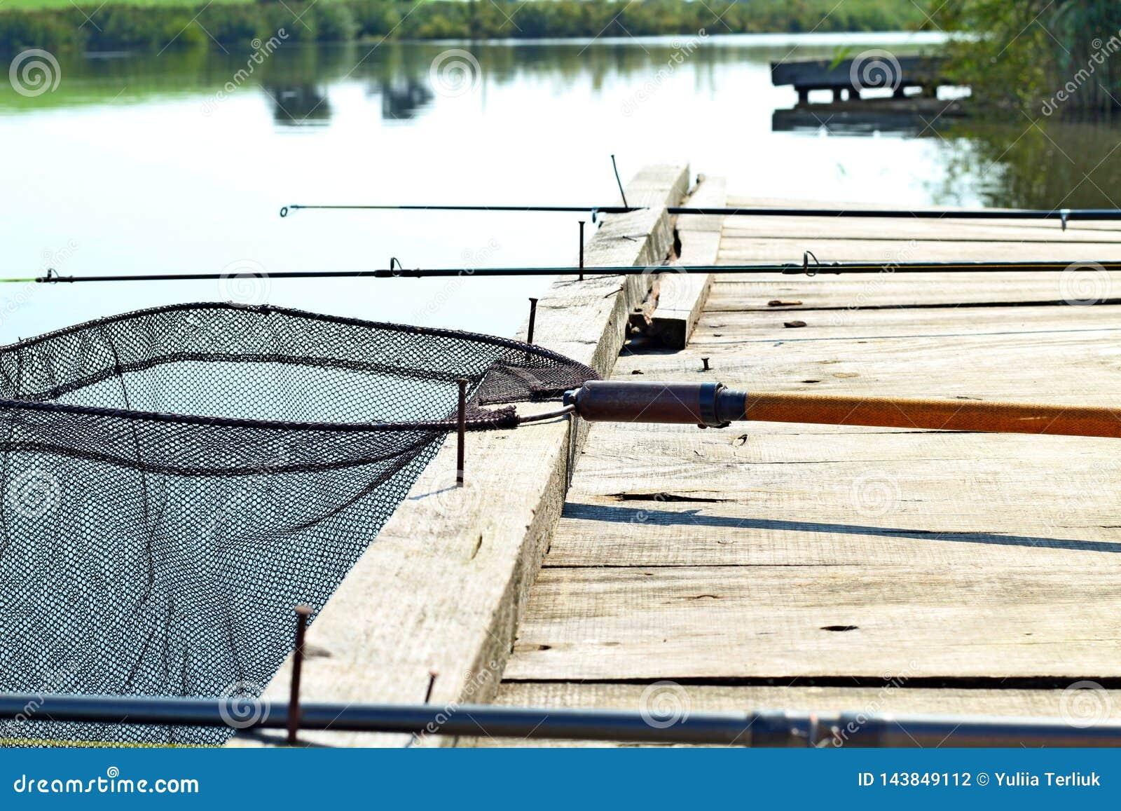Fundo da pesca Imagem tonificada retro do equipamento de pesca no cais de madeira Pescando a plataforma no lago