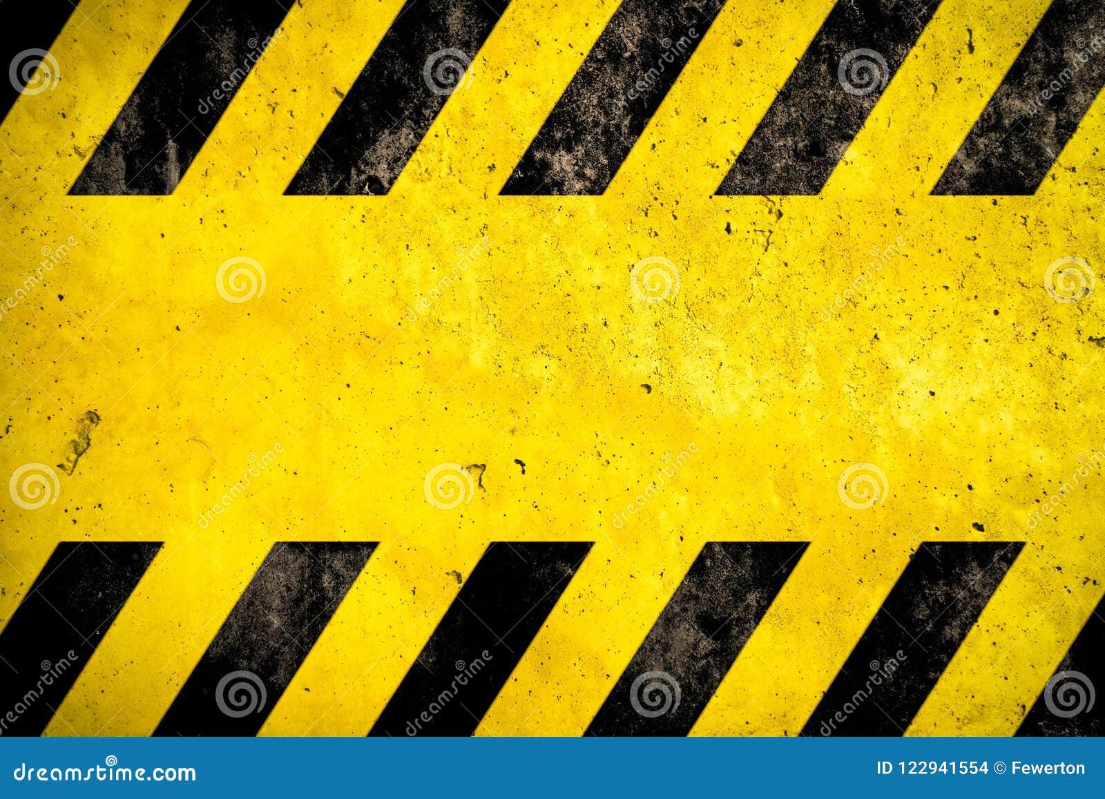 Fundo de advertência com as listras amarelas e pretas pintadas sobre a textura amarela da fachada do muro de cimento e o espaço v