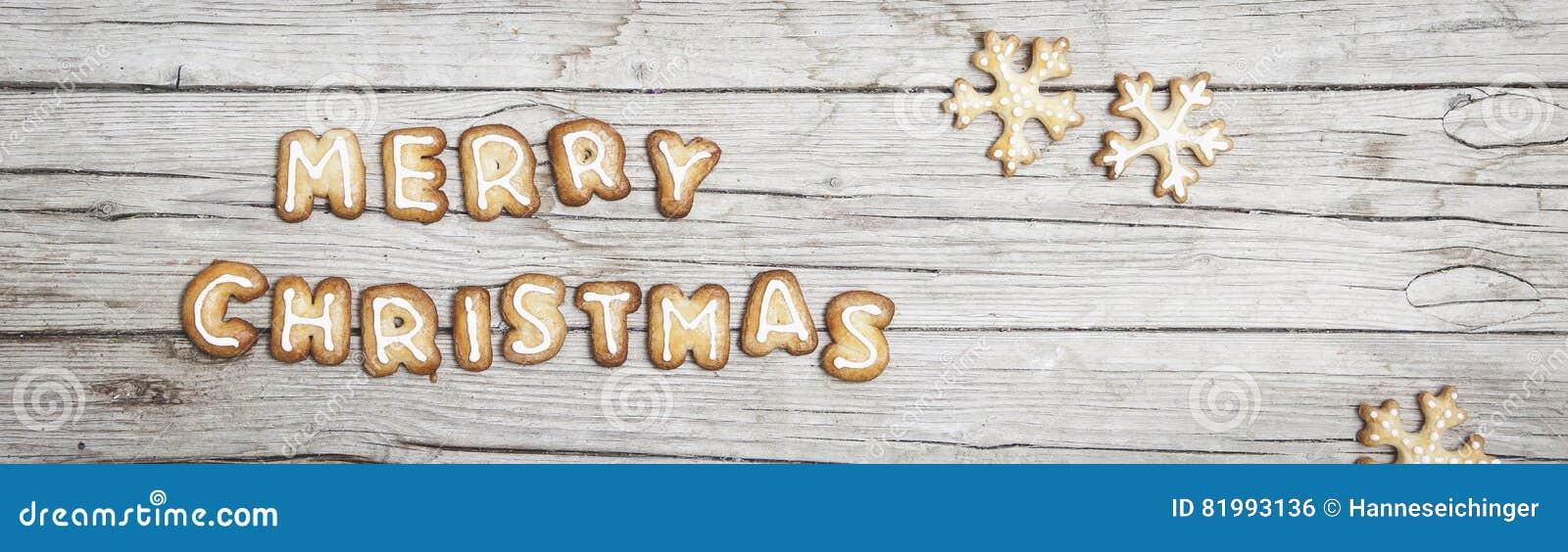 Fundo de madeira cinzento de Christmassy com pão-de-espécie e letra alegre do ` s de Christma