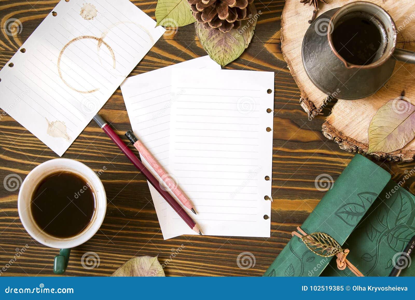 Fundo de madeira com papel para notas, leiteria, cofee, ezve do  de Ñ, cone, folhas de outono Opinião superior do local de traba