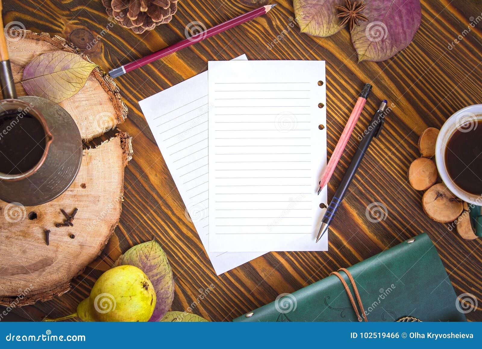 Fundo de madeira com papel para notas, leiteria, cofee, ezve do  de Ñ, folhas de outono Opinião superior do local de trabalho