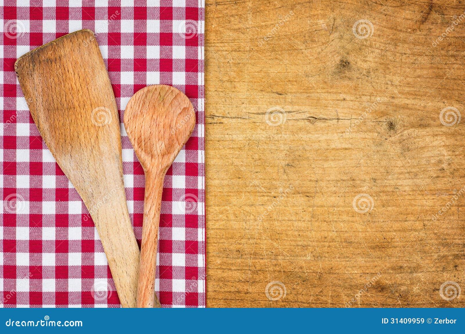 Fundo de madeira rústico com uma toalha de mesa quadriculado e umas colheres de madeira