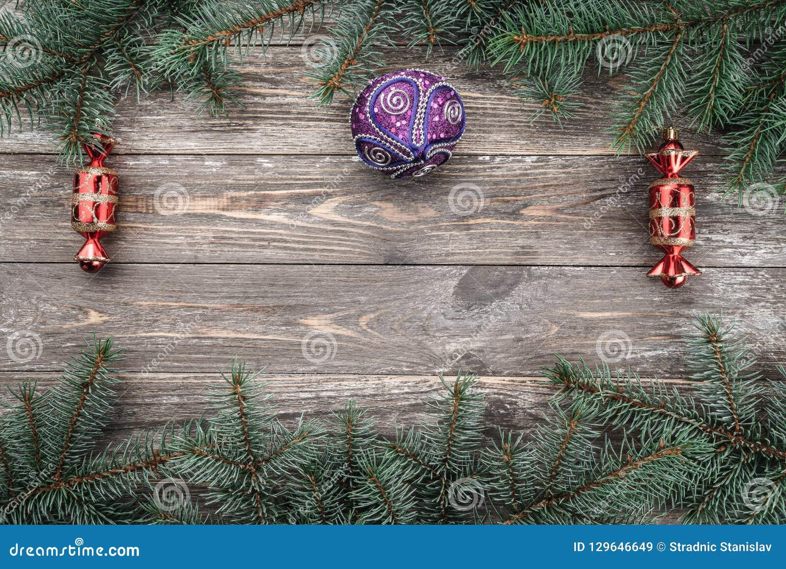 Fundo de madeira velho com ramos do abeto com brinquedos Espaço para uma mensagem do cumprimento Cartão de Natal Vista superior