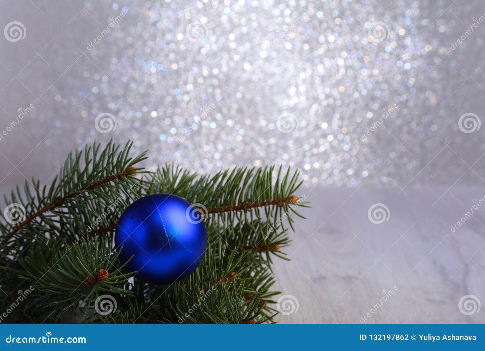 Fundo decorativo com ramos do abeto e as bolas azuis na prata Conceito do feriado do cartão de Natal