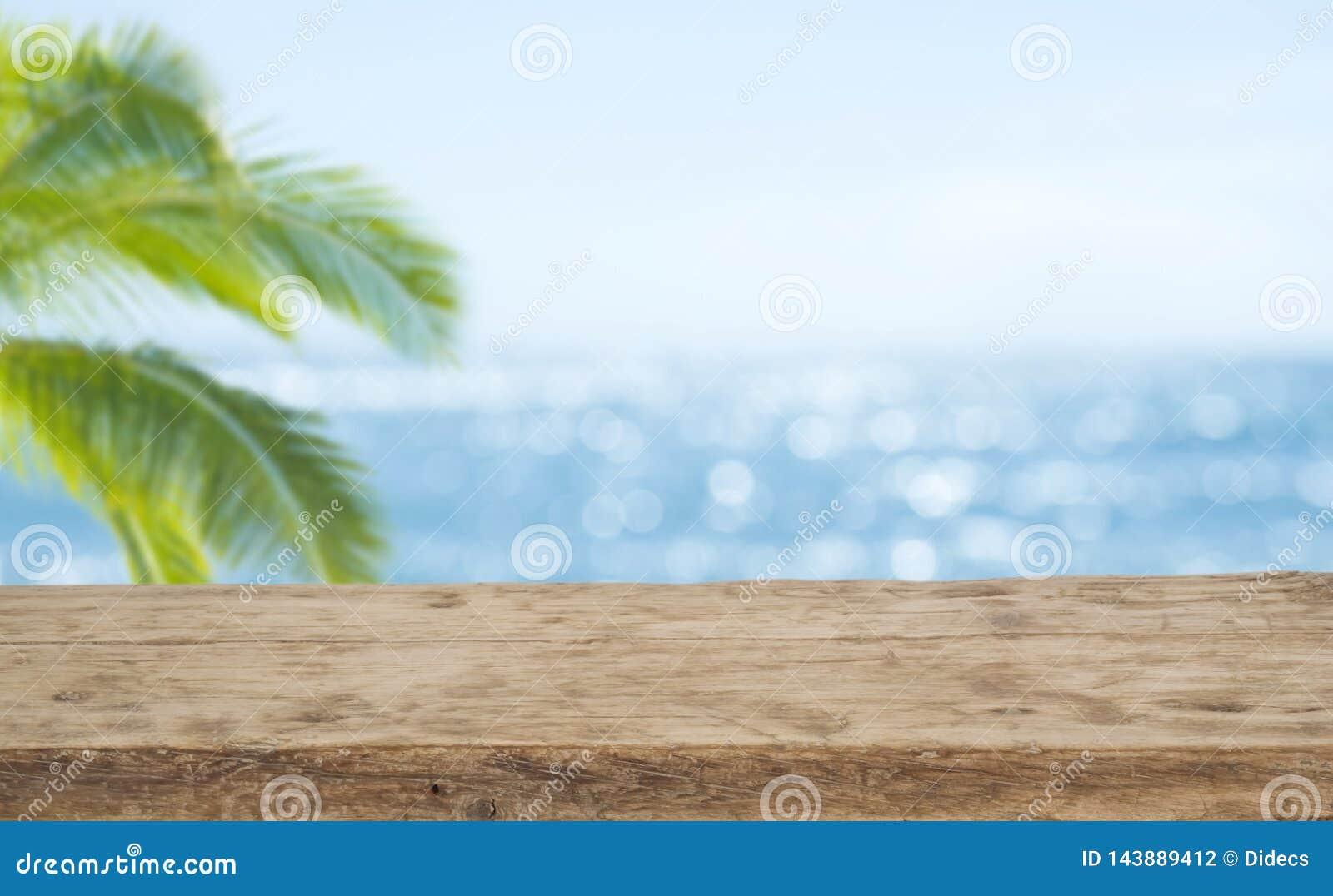 Fundo Defocused do mar com primeiro plano de madeira da tabela para a exposição do produto