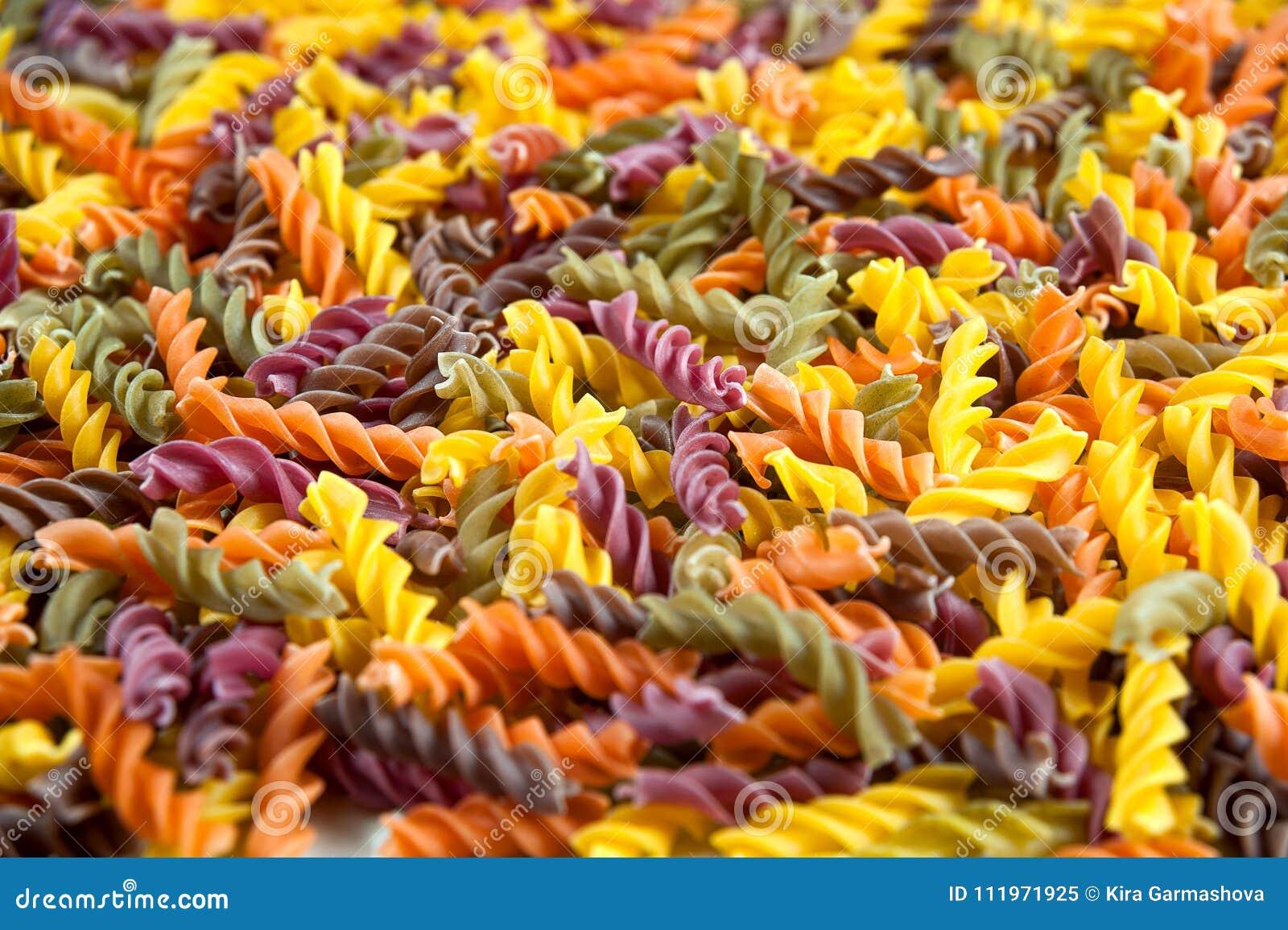Fundo do alimento - massa três-colorida cru do trigo de trigo duro de Fusilli com espinafres e tomate