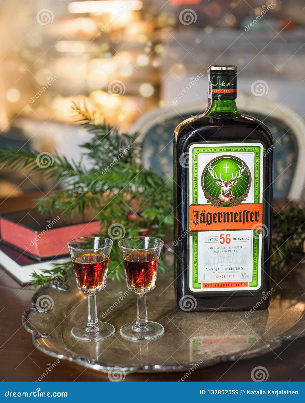 Fundo do ano novo feliz ou do Natal com bebida do álcool de Jagermeister, elixir Garrafa de Jagermeister com vidros em um vintage