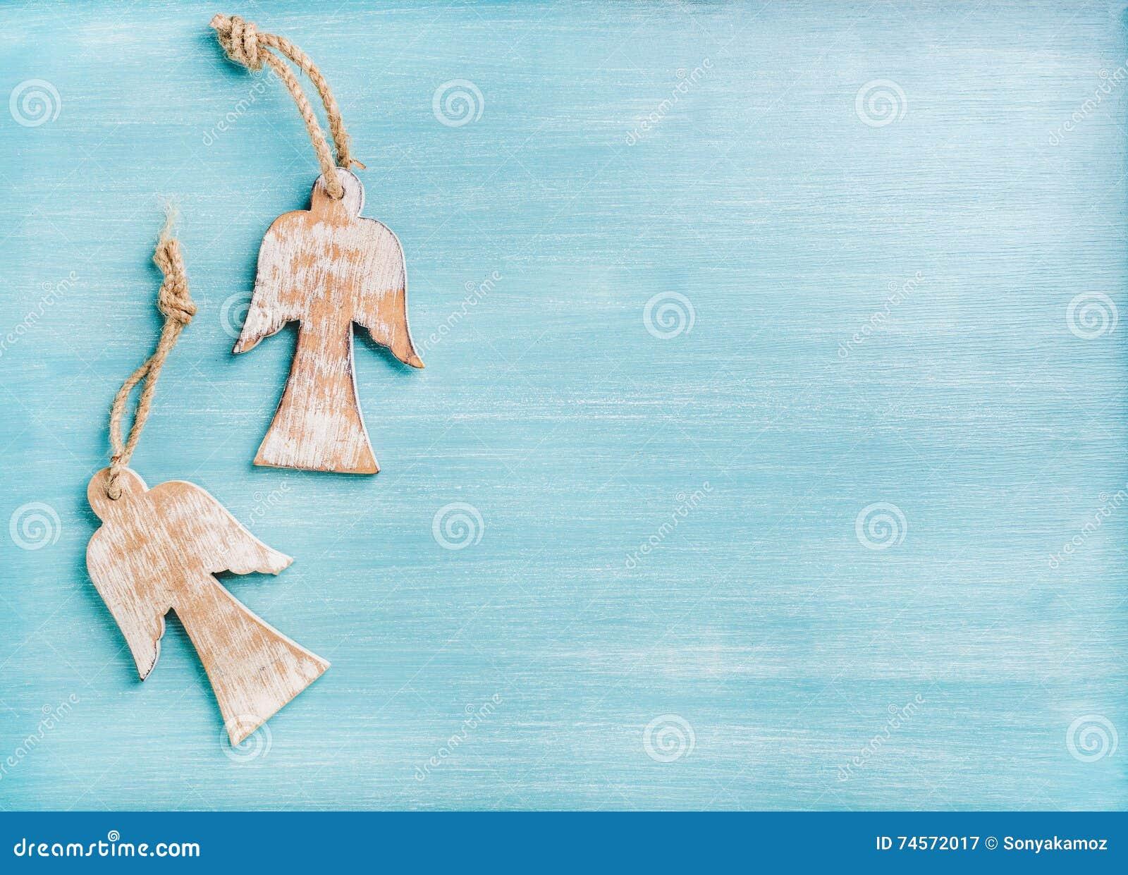Fundo do ano novo ou do Natal: dois anjos de madeira sobre o azul pintaram o contexto, espaço da cópia