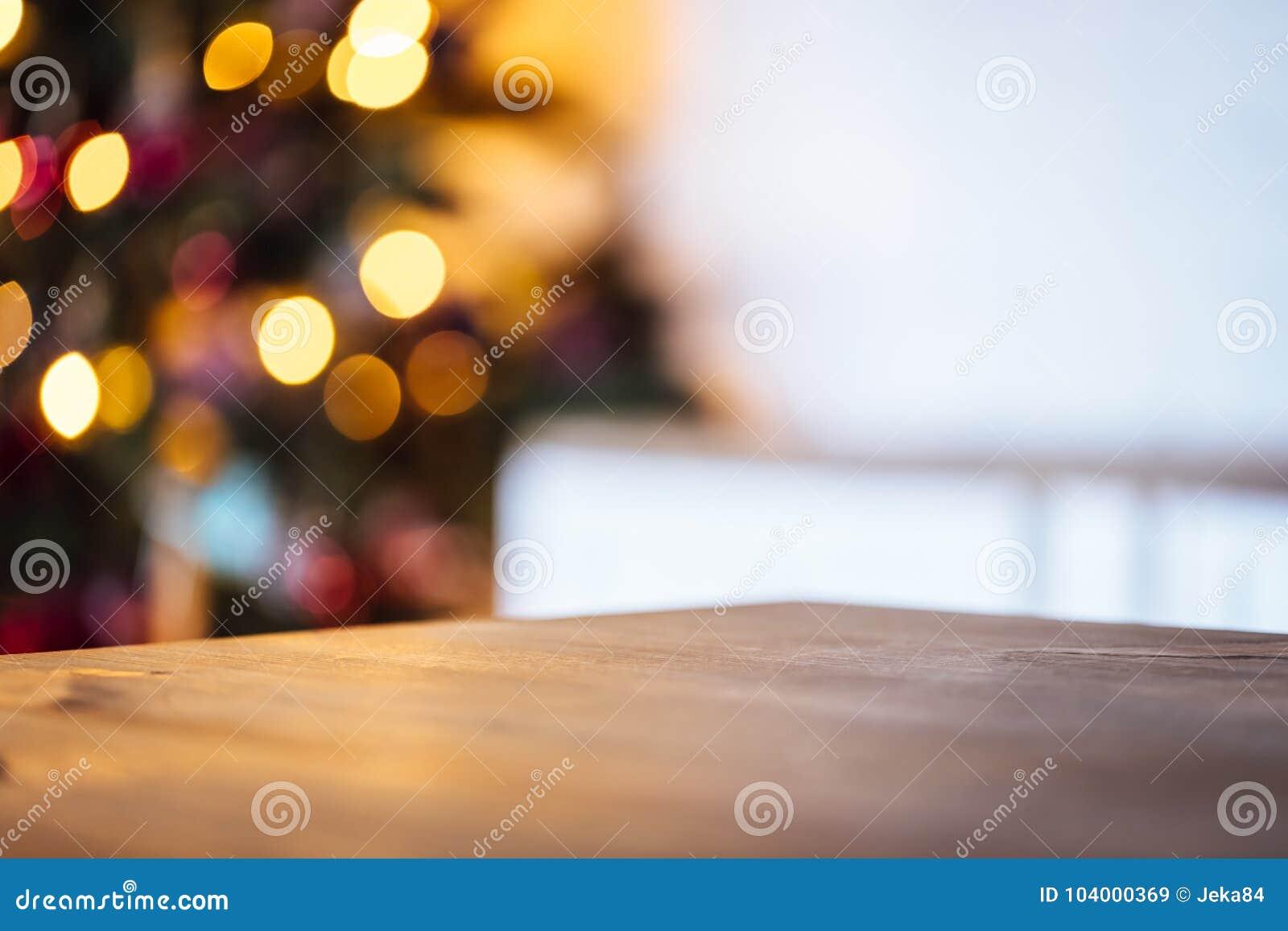 Fundo do feriado do Natal com a tabela rústica vazia e o bokeh da sala de visitas com a árvore de Natal